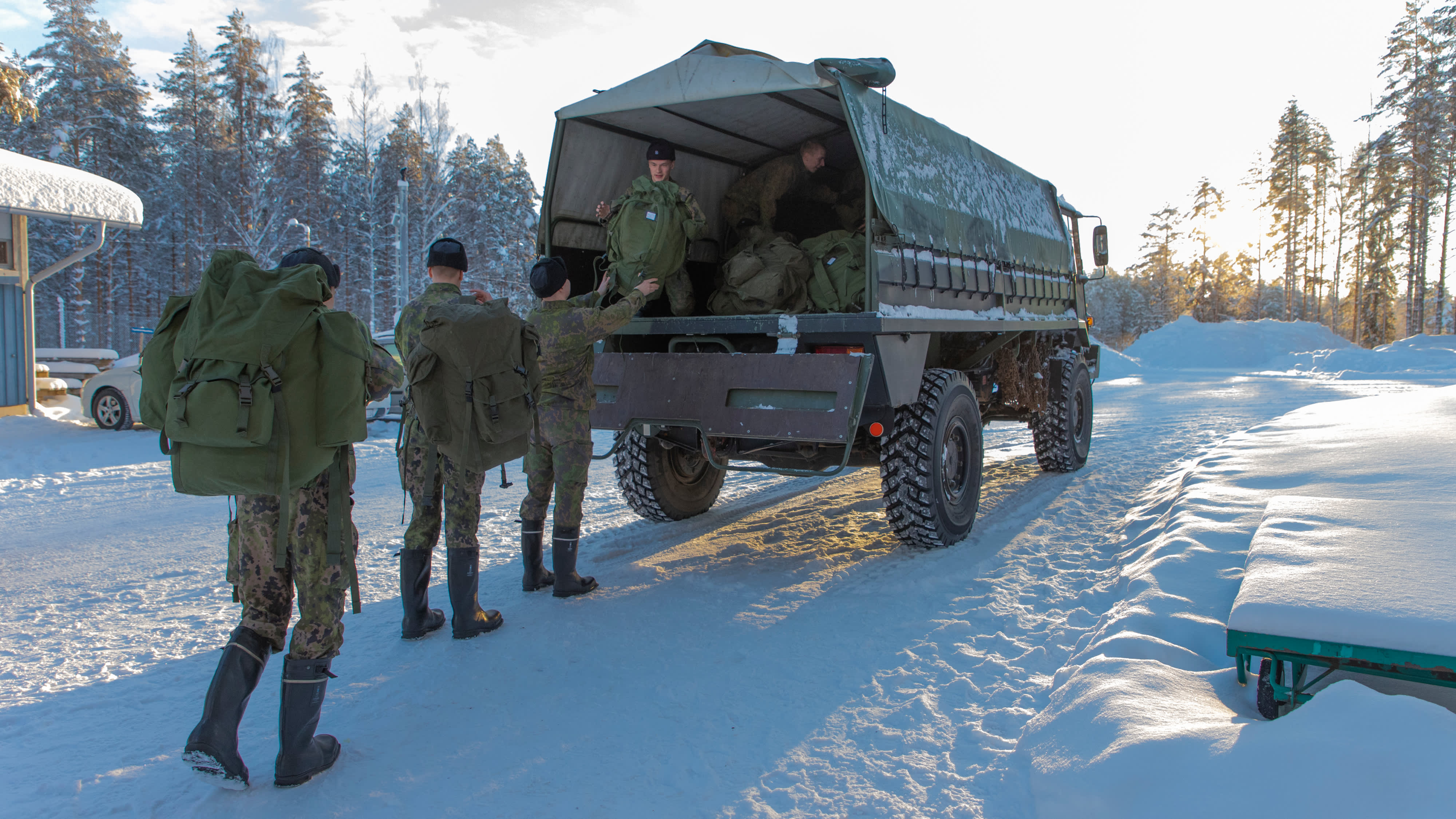Varusmiehet pakkaavat reppuja Masi maastoautoon