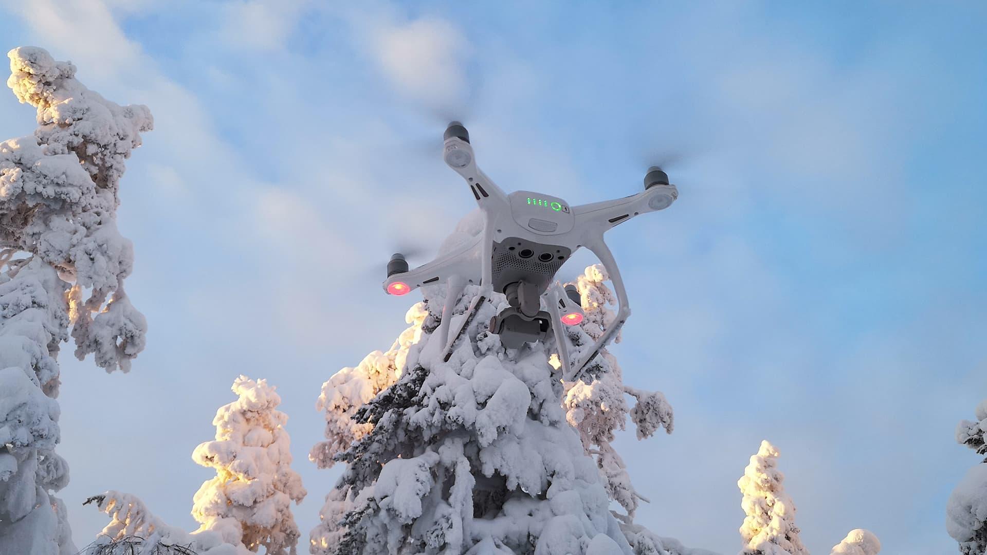 Drone lentää talvista taivasta vasten.