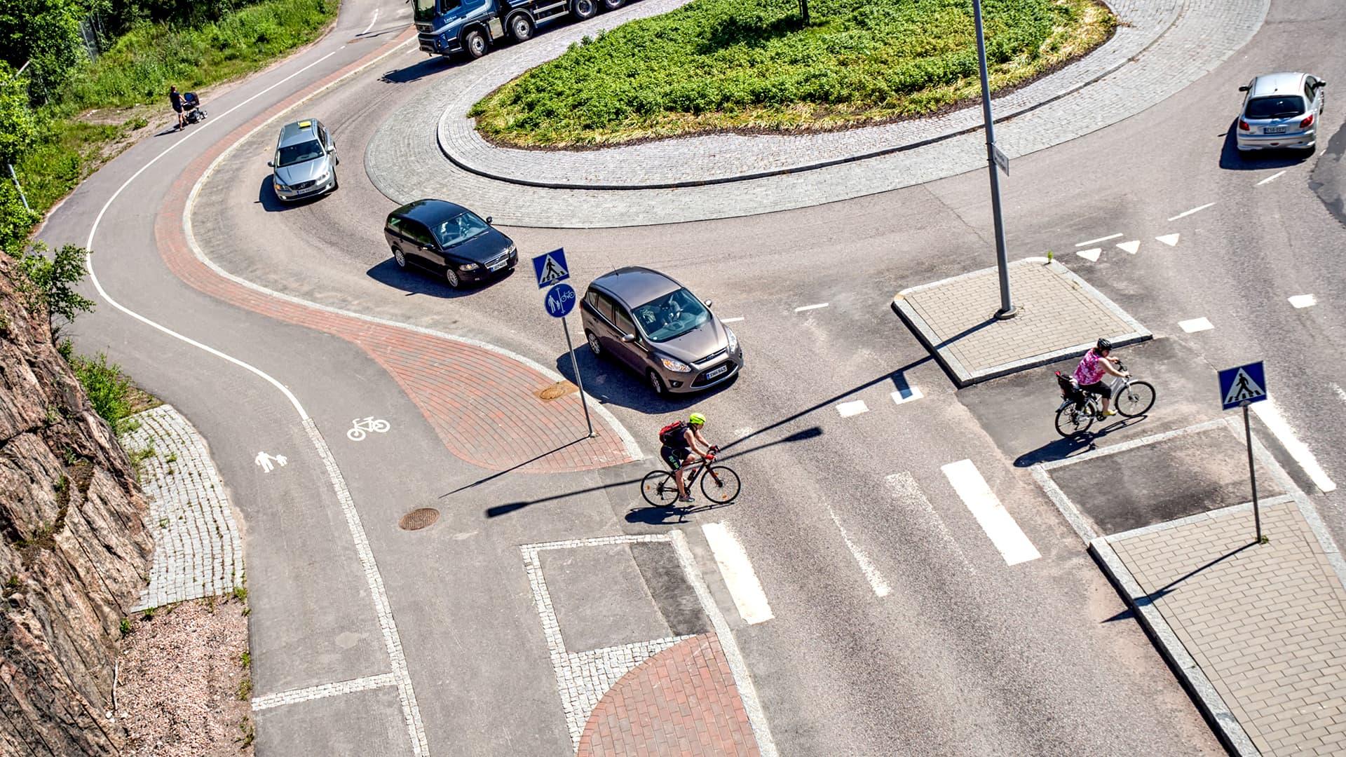 Autoja ja pyöräilijöitä liikenneympyrässä.