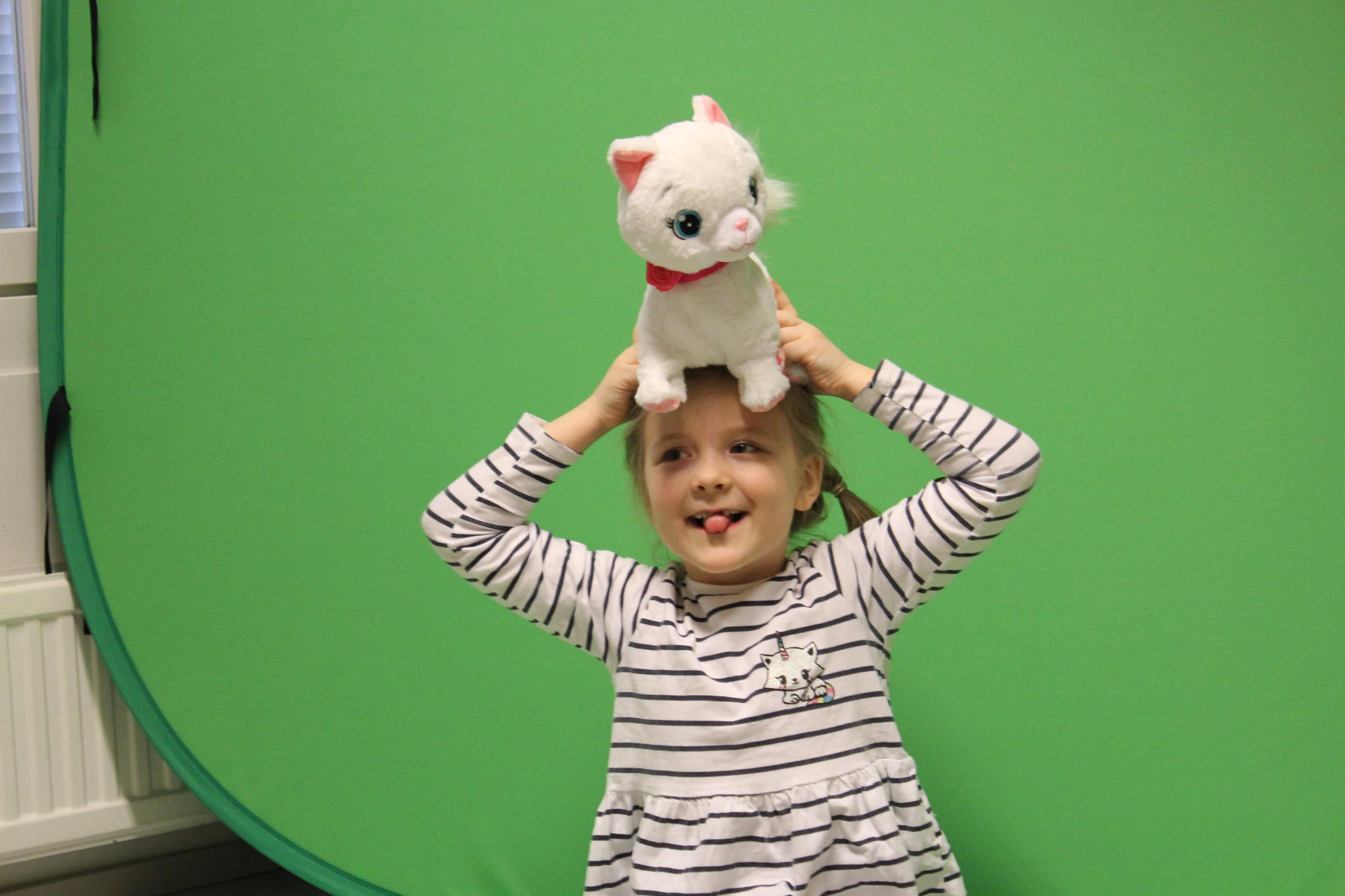 Lapset ottavat toisistaan kuvia green screen -kankaan edessä.