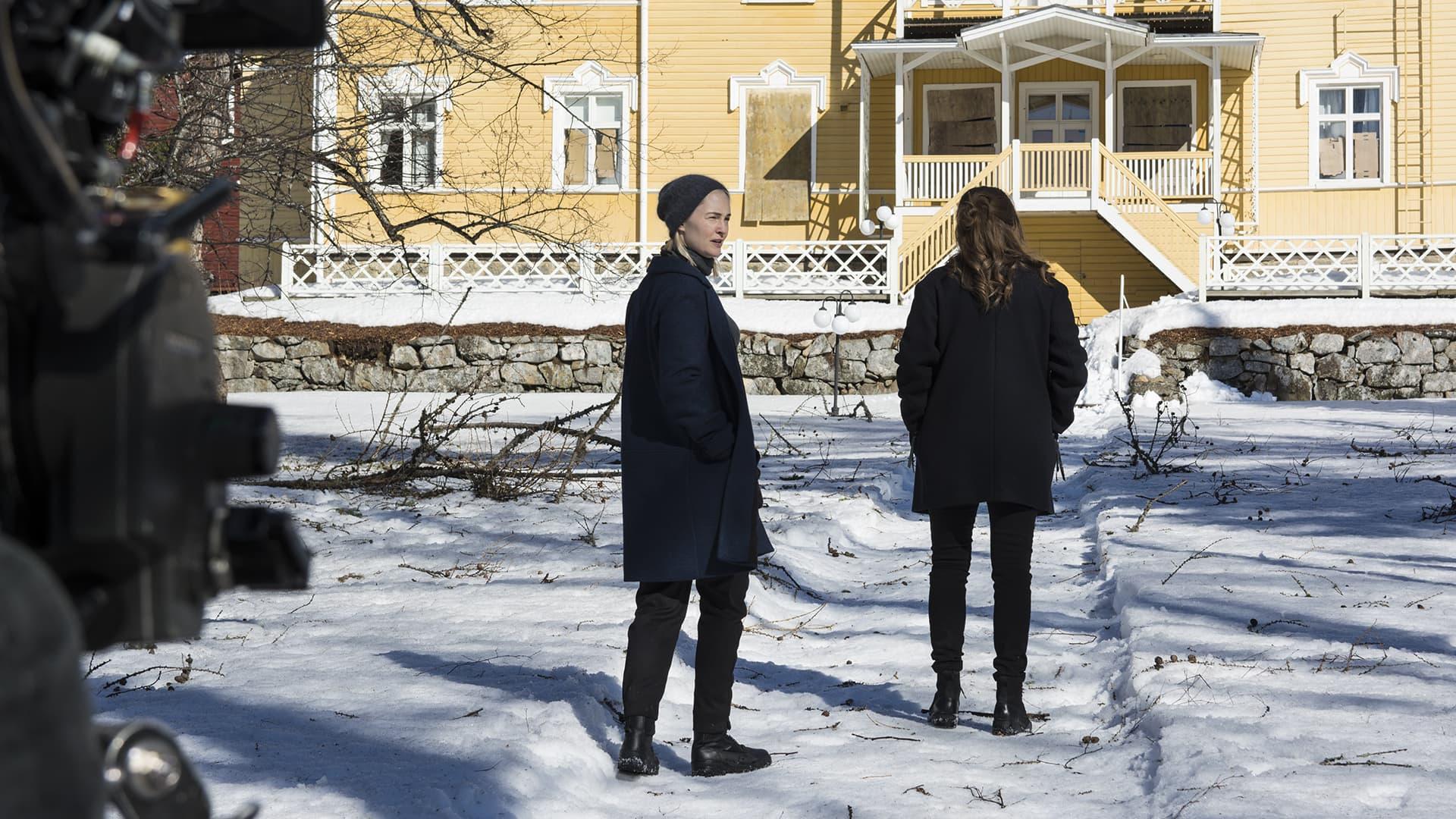 Näyttelijät televisiosarjan kuvauksissa vanhan kartanon lumisella pihalla.