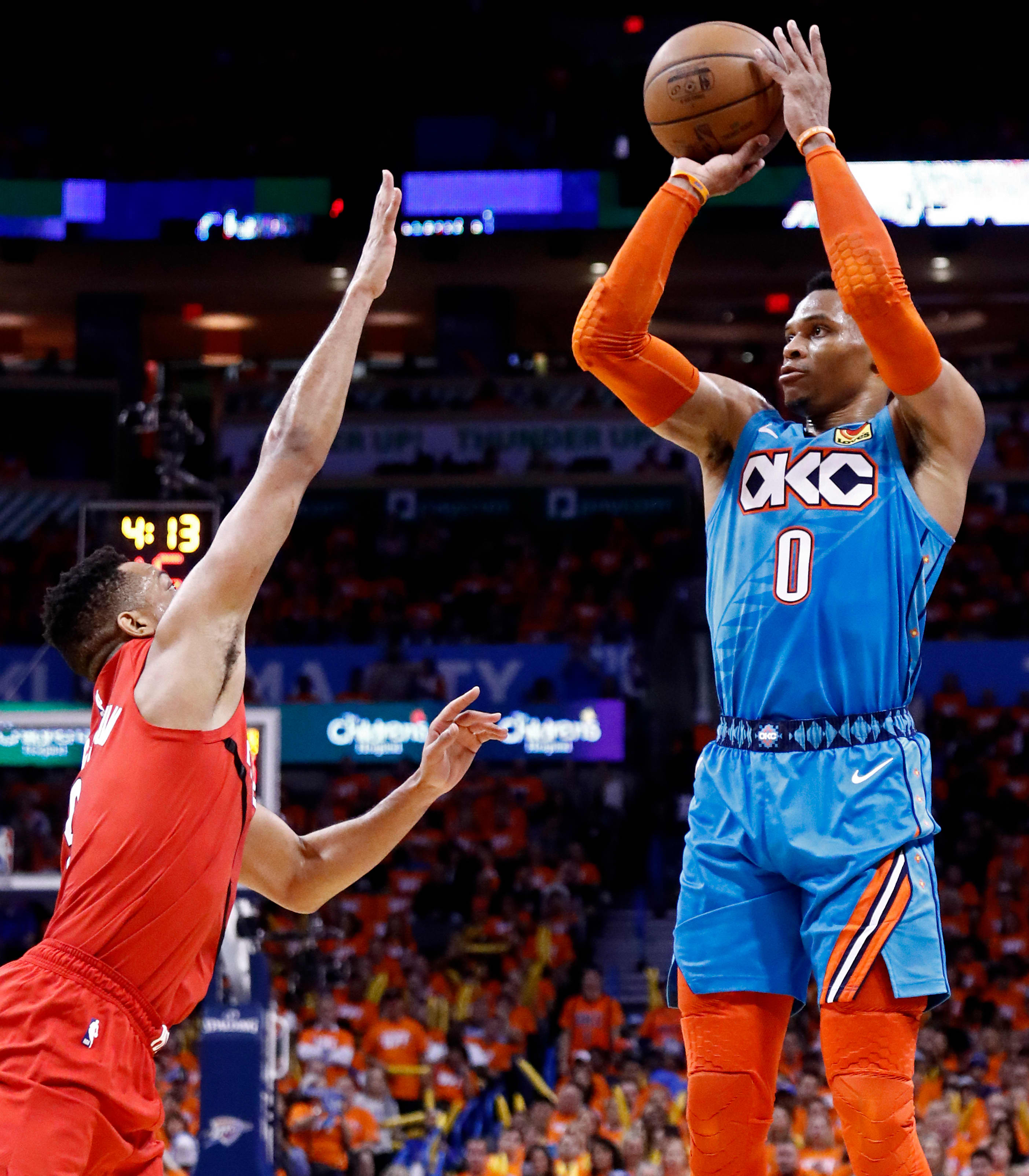 Portland Trail Blazers player CJ McCollum (L) tries to block a shot against Oklahoma City Thunder player Russell Westbrook