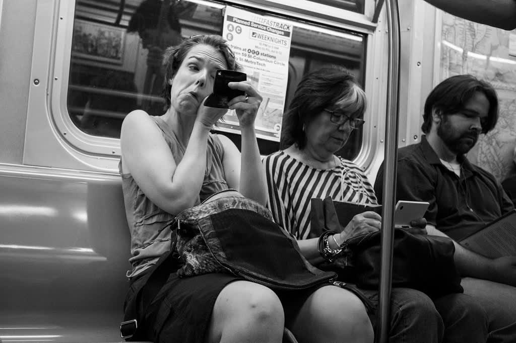 Mustavalkoinen kuva naisesta, joka peilaa ja laittaa silmämeikkiä metrossa.