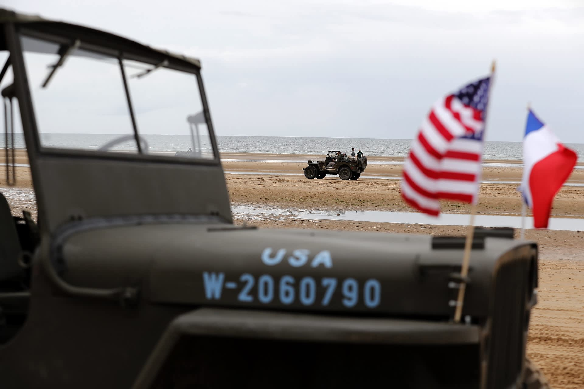Yhdysvaltain ja Ranskan liput jeepin keulassa. Taustalla ranta ja meri.