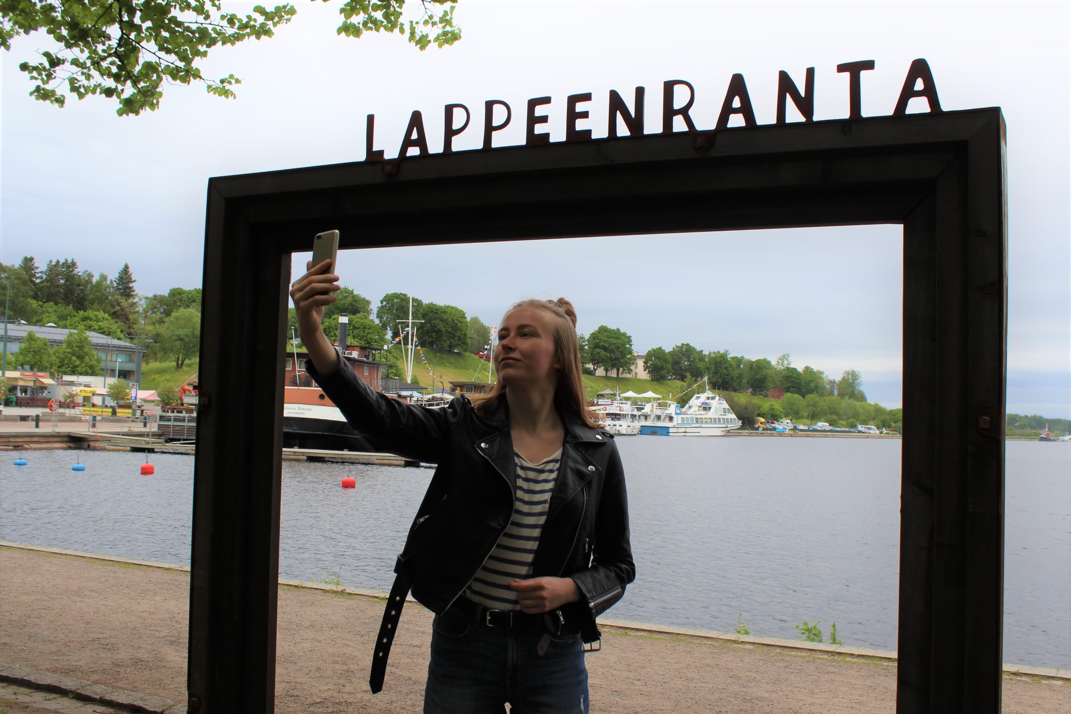 Hanna Muukkonen ottaa itsestään valokuvan Lappeenrannan maisemakehyksissä.