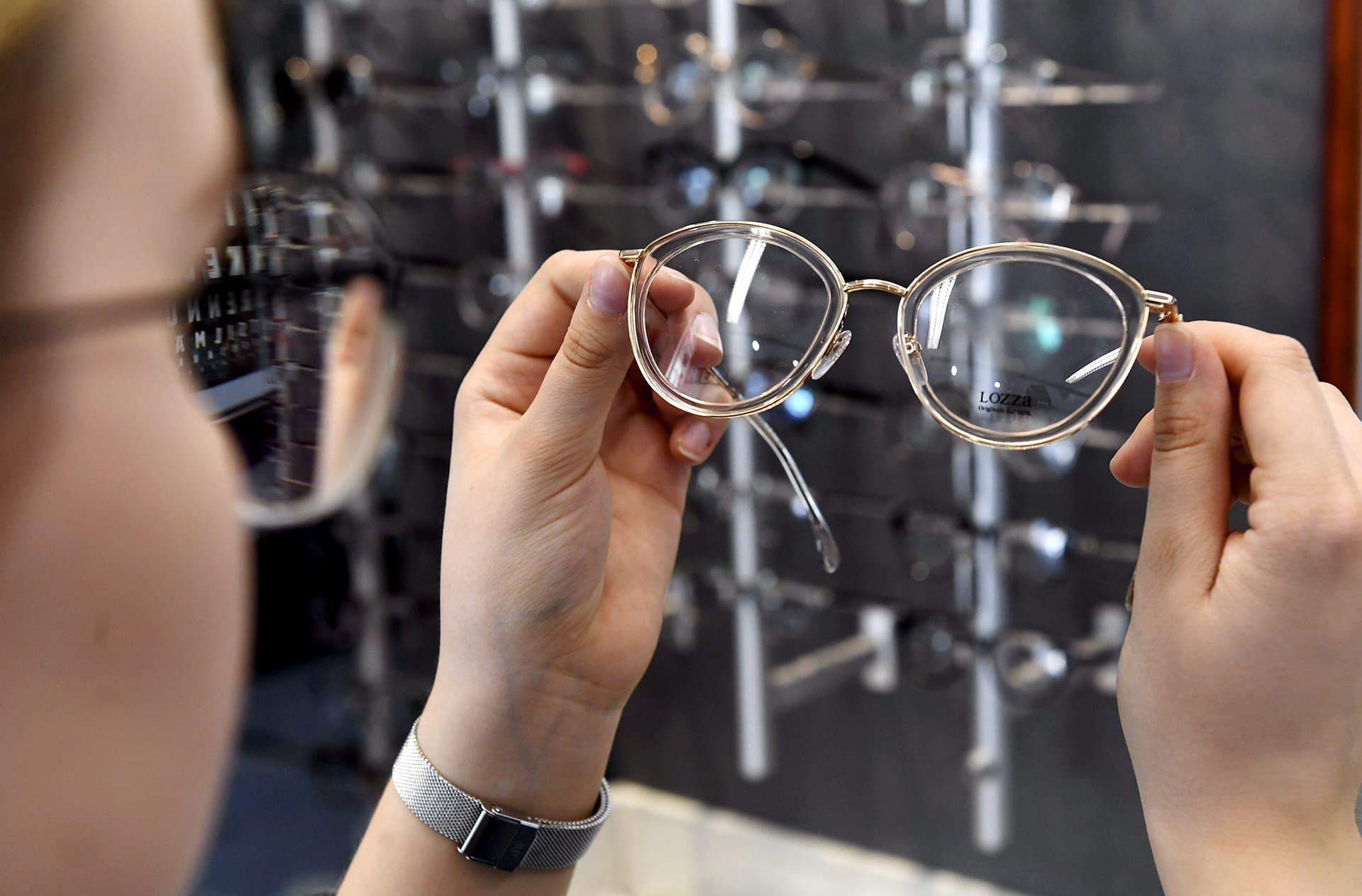 Nainen tutkii kehyksiä silmälasiliikkeessä.