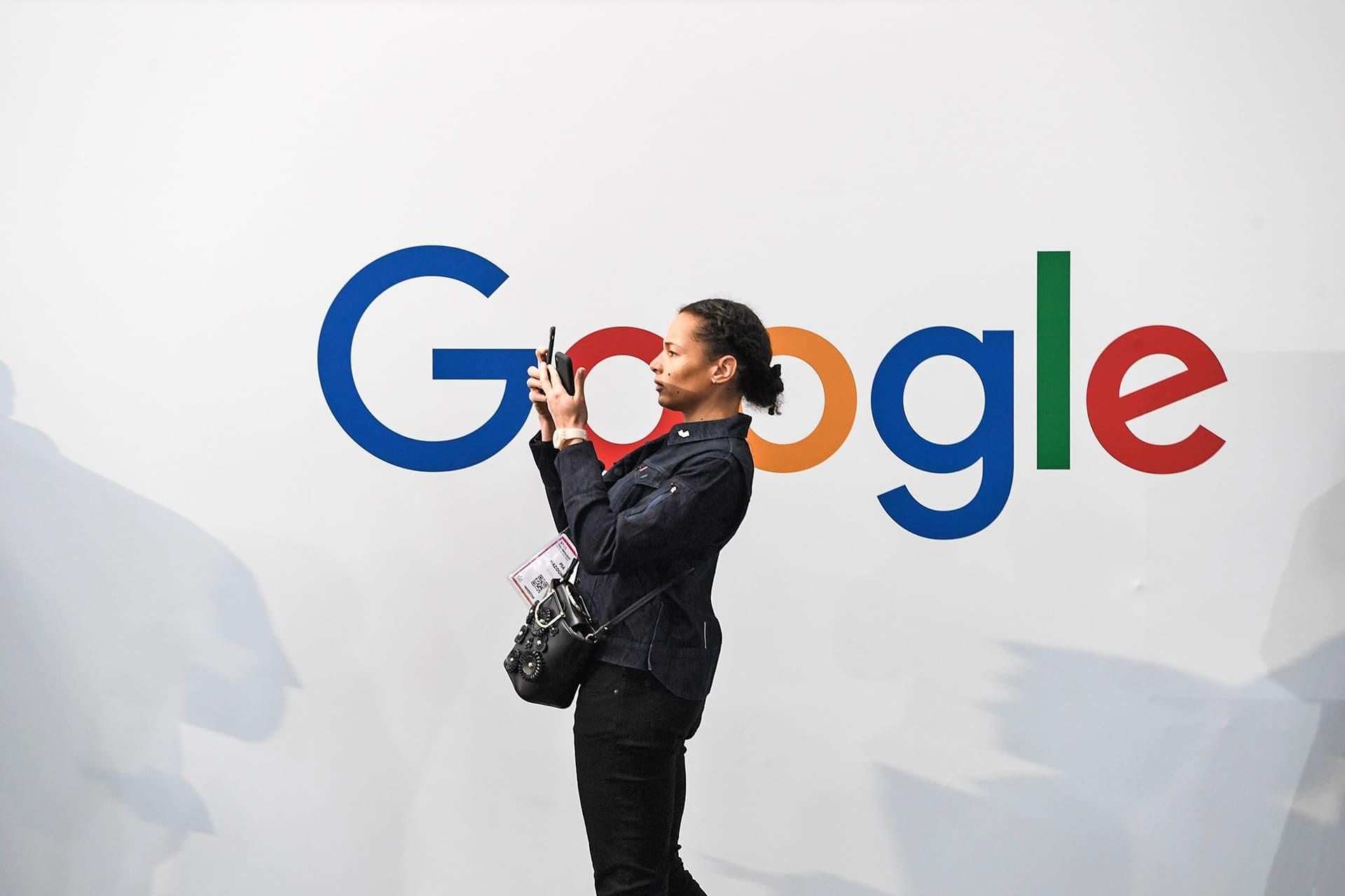 Nainen ottamassa selfietä.  Taustalla olevalla valkoisella seinällä on Googlen logo.