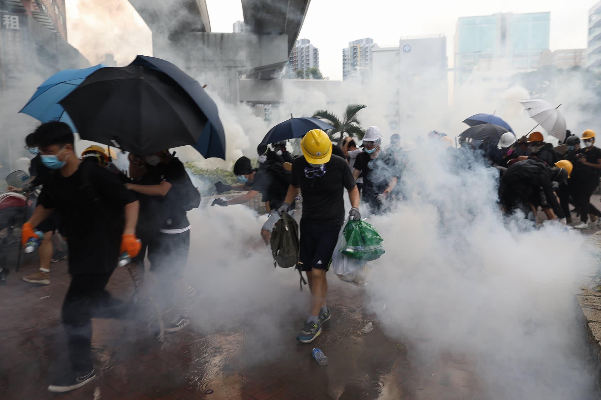 Mielenosoittajat suojautuvat sateenvarjoilla.