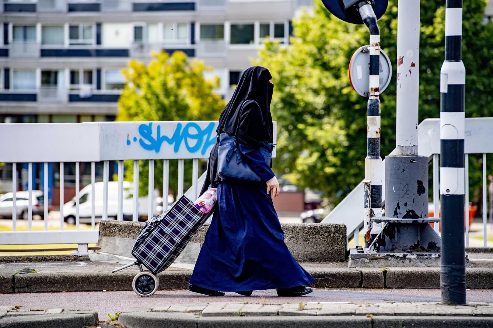 Naaman osittain peittävään nikabiin pukeutunut musliminainen Rotterdamissa, Hollannissa.