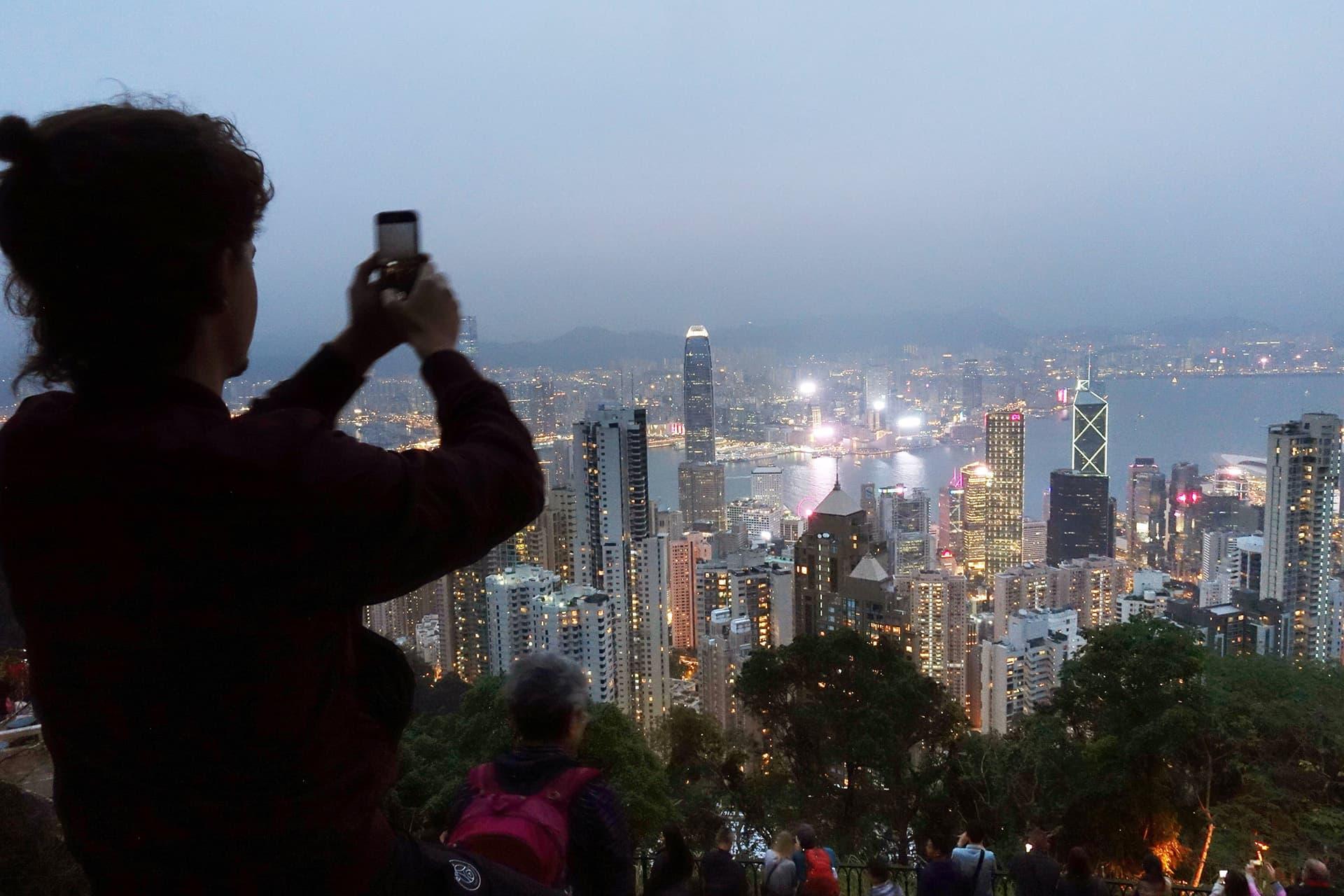 Turisti kuvaa näkymän Hongkongin keskusta Victoria Peakin huipulta.