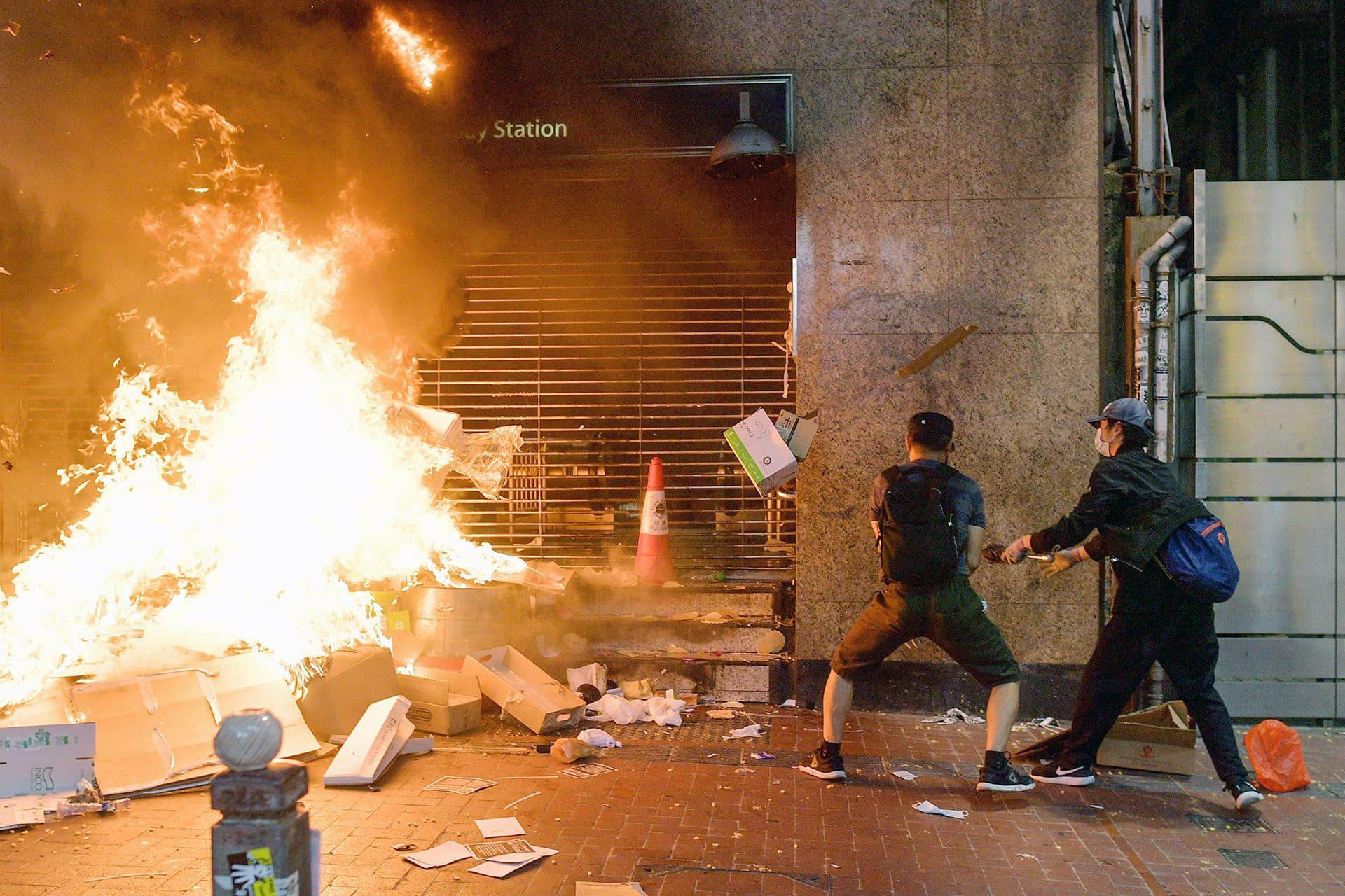 Mielenosoittajat polttavat tavaroita kadulla Hongkongissa.