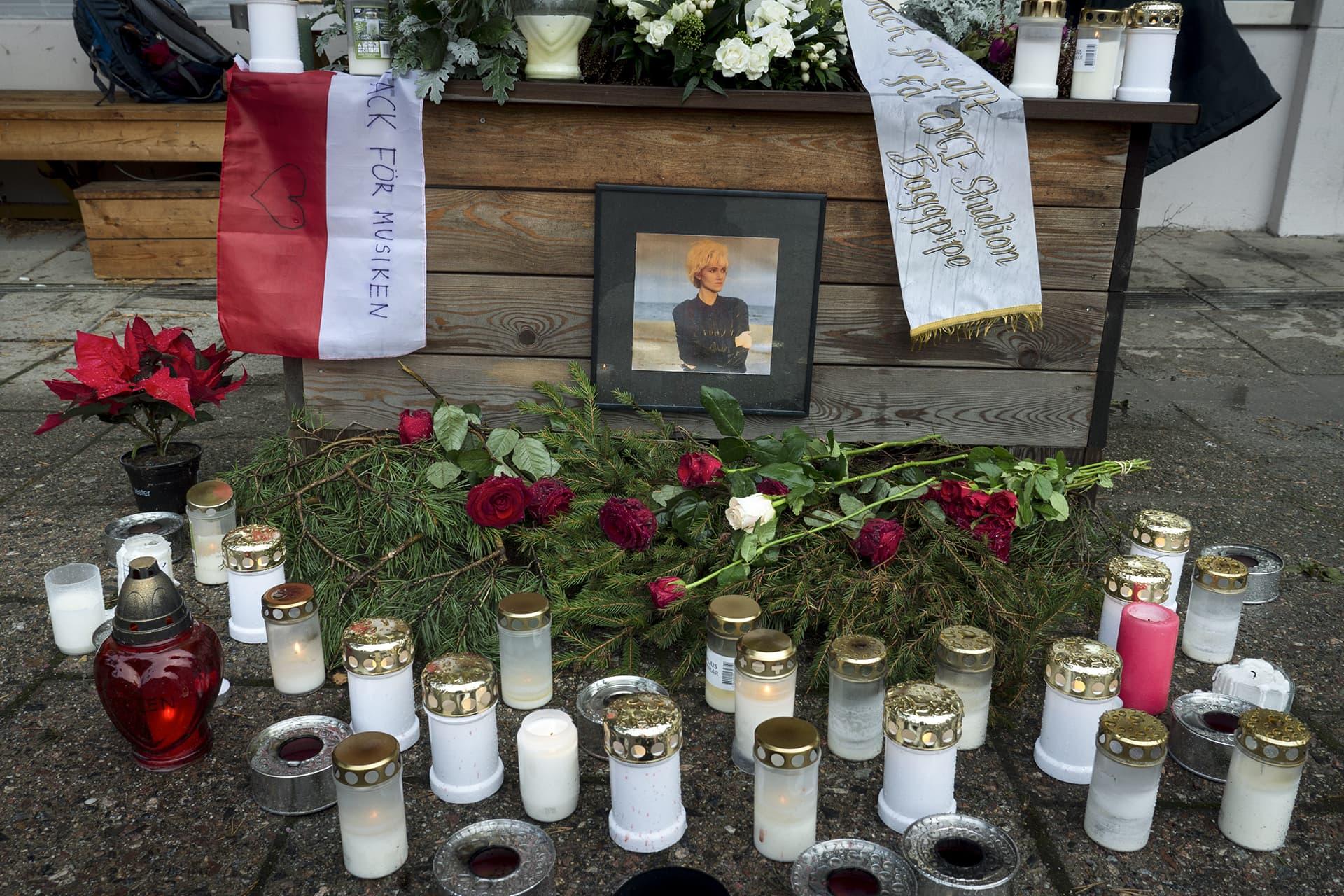 Kynttilöitä ja muistokukkia, sekä Marie Fredrikssonin kuva keskellä.