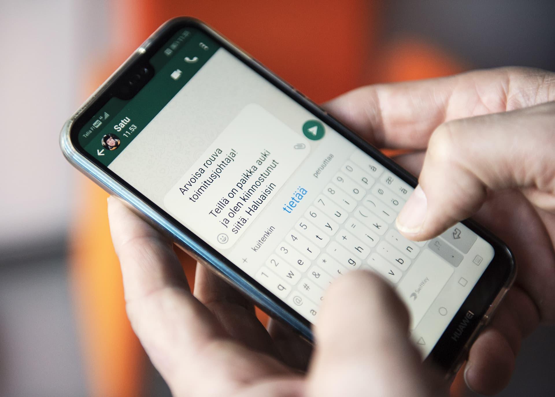 mies näpyttelee tekstiä älypuhelimella