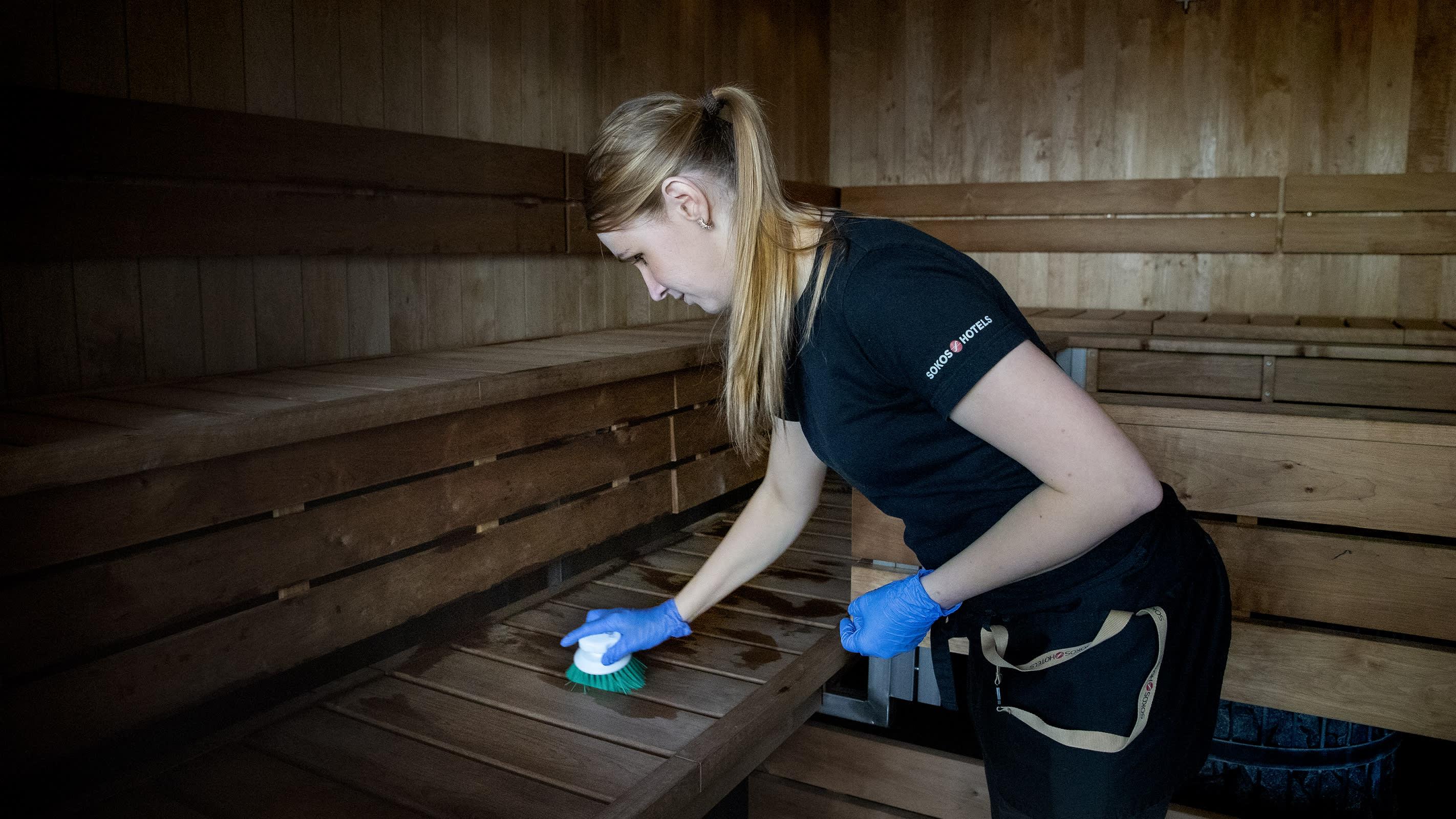 Siivooja jynssää pyöräharjalla Hotelli Paviljongin miesten saunan lauteita Jyväskylässä.