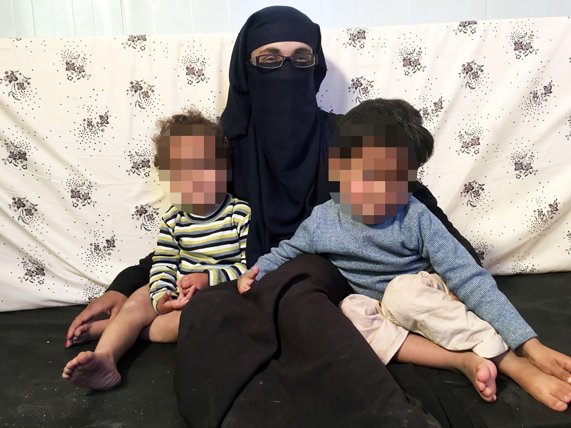 Terrorismista epäilty norjalainen nainen ja hänen kaksi lastaan istuvat lähellä toisiaan. Lasten kasvot on kuvankäsitelty tunnistamattomiksi.