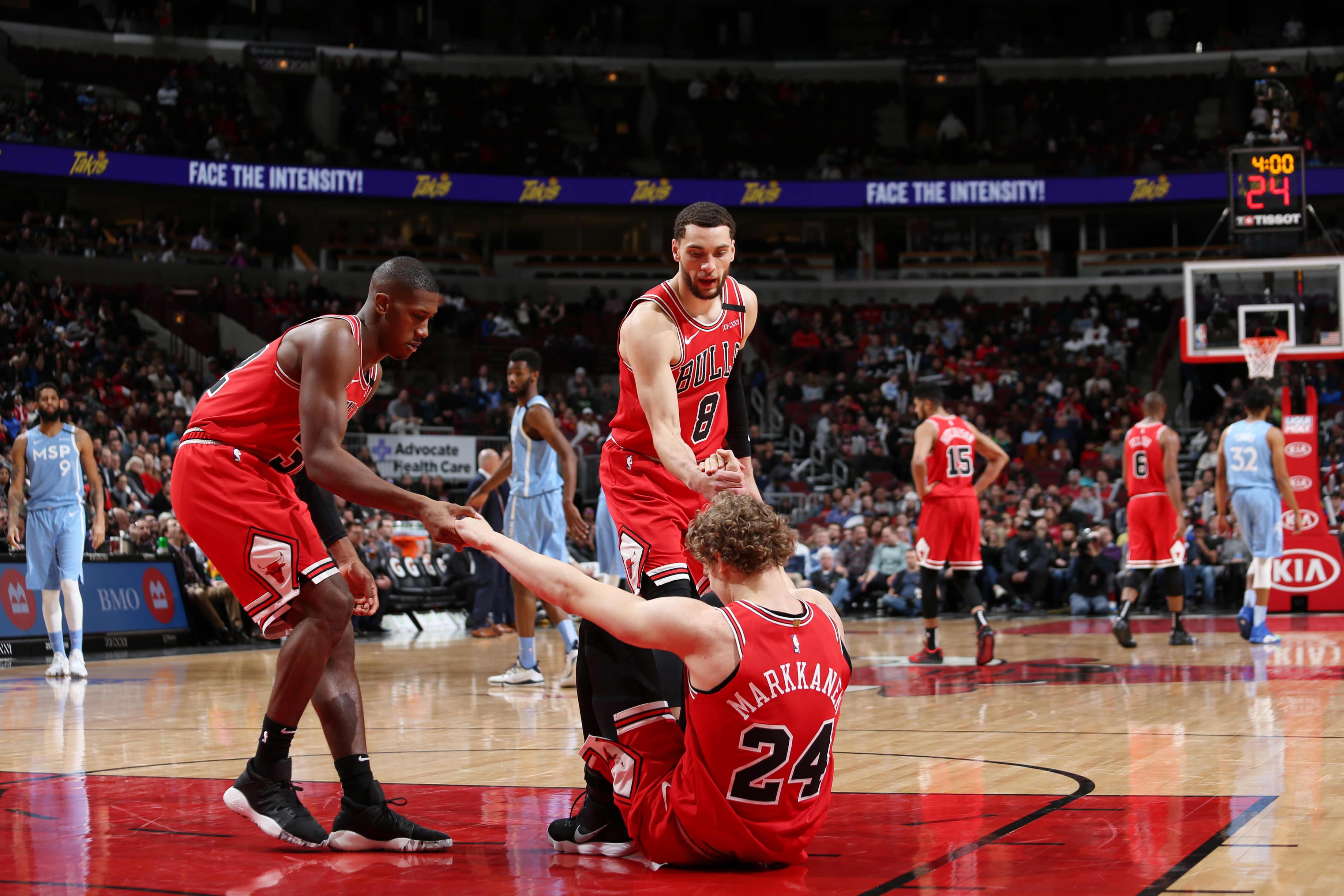 Chicago Bullsin Kris Dunn ja Zach LaVine auttavat tuskaista Lauri Markkasta ylös koripalloparketilla.