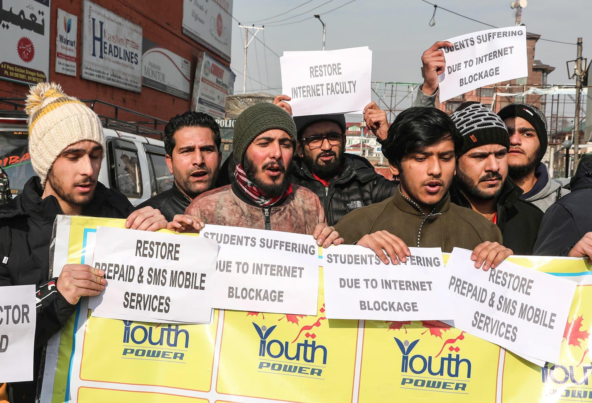 Kashmirilaiset nuoret pitävät kylttejä joissa kritisoidaan puhelin- ja internetpalveluiden katkaisemista.