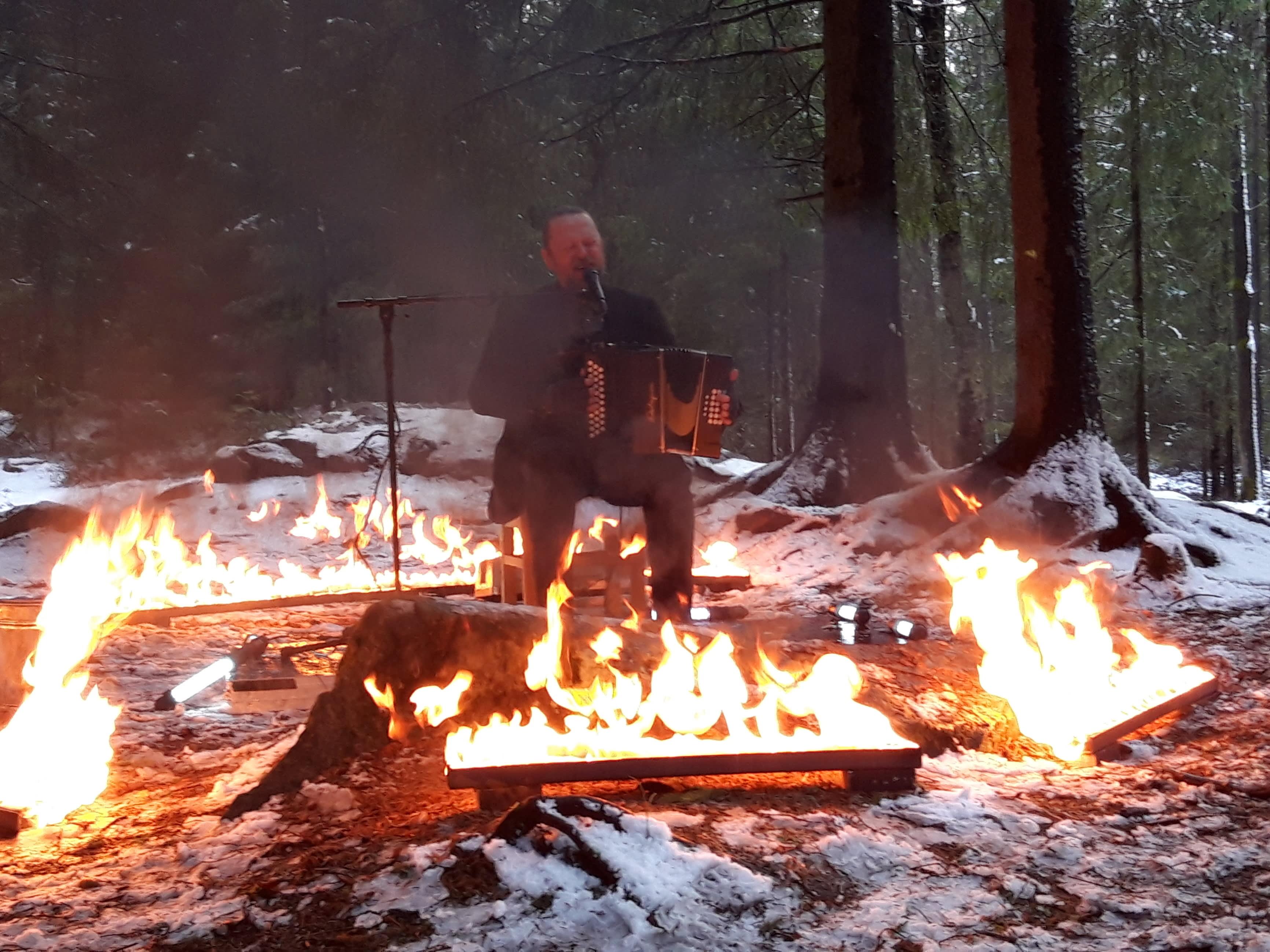 Taiteilija Antti Paalanen soittaa metsässä.