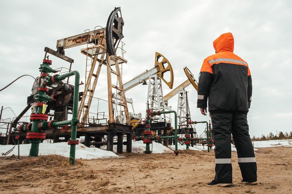 Etualalla työntekijä seisoo elin kameraan. Taustalla on kolme öljypumppua.