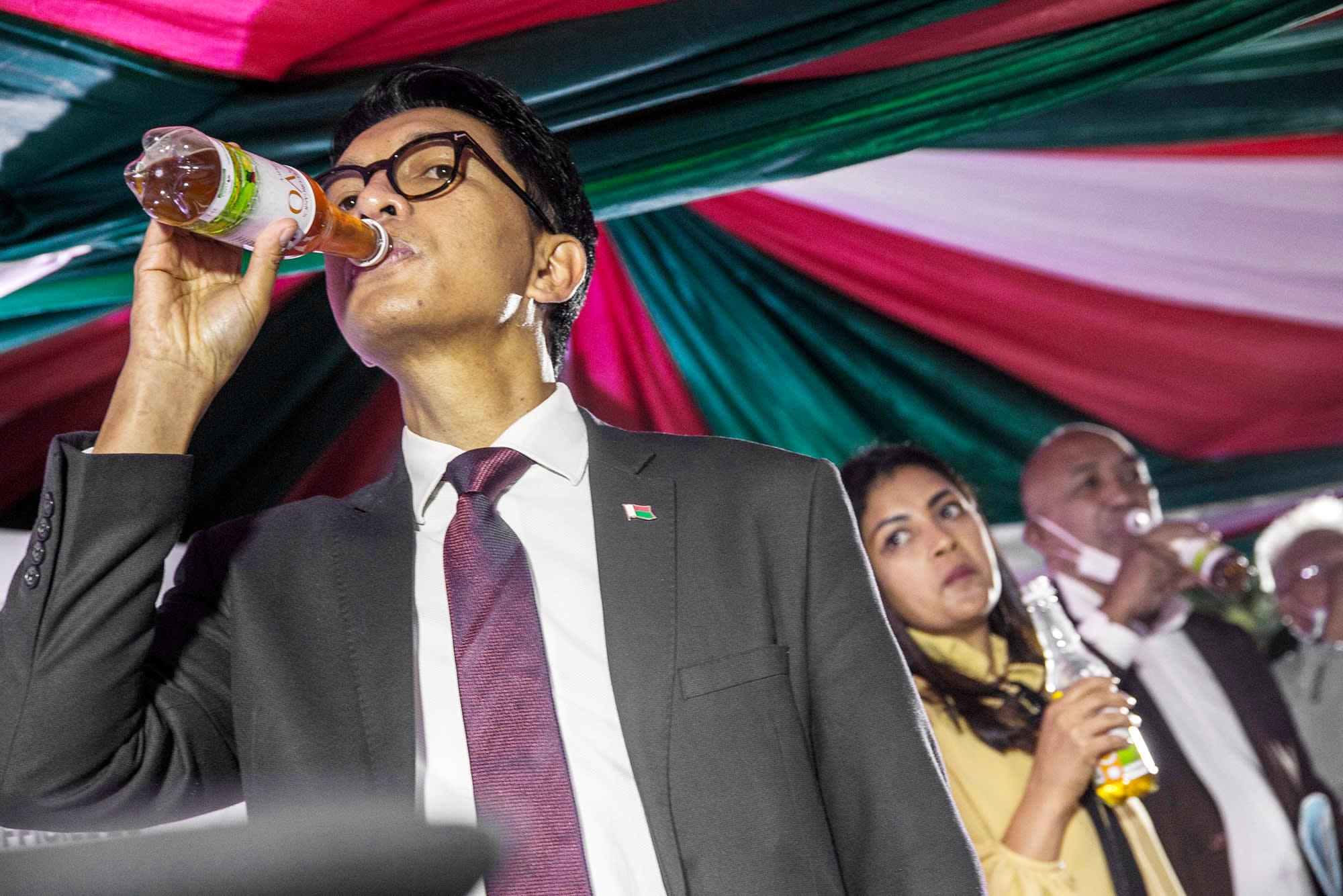 Andry Rajoelina juo yrttiteetä pullon suusta.