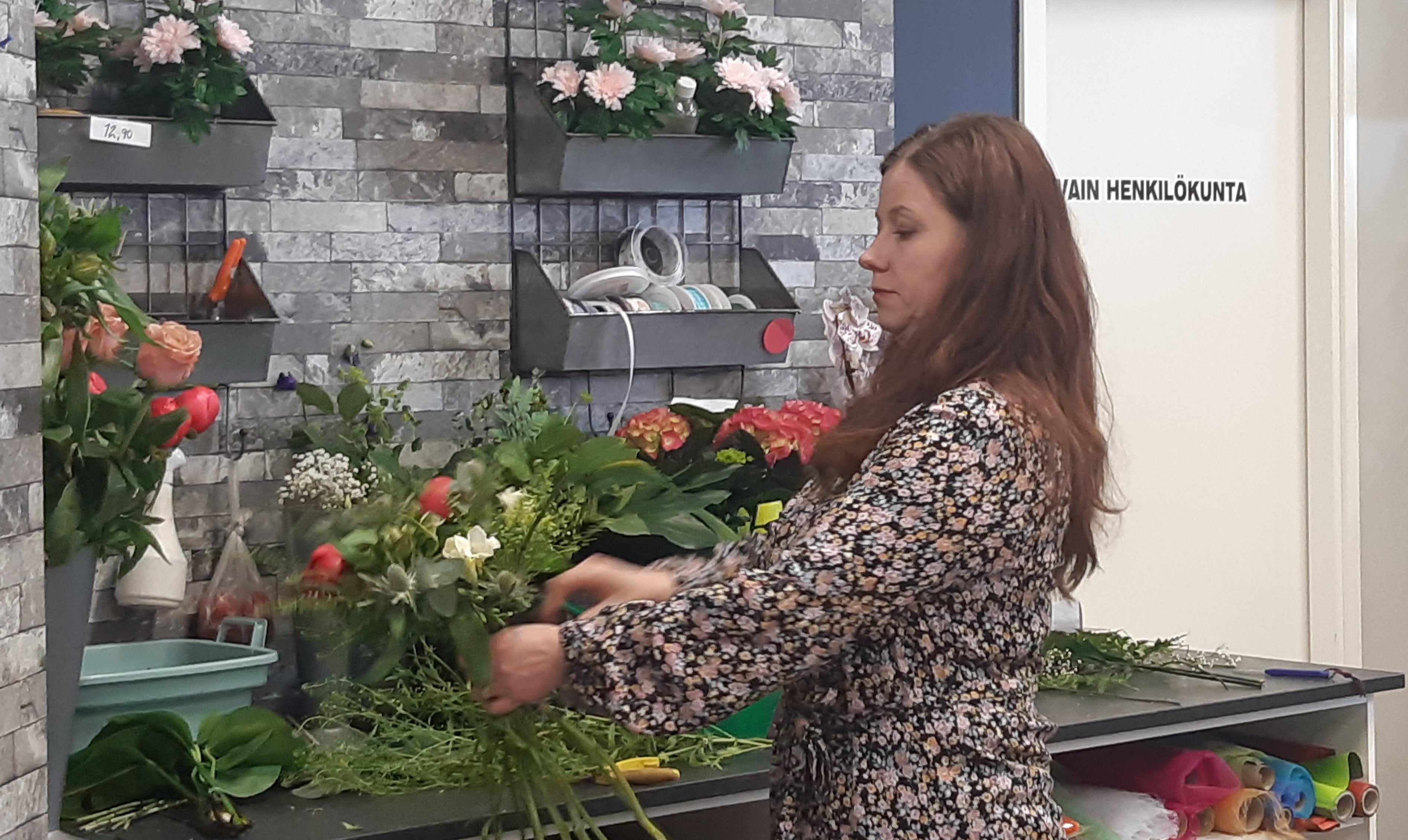 Kemiläisen Linja-Kukan yrittäjä Johanna Åhman sitoo kukkakimppua.