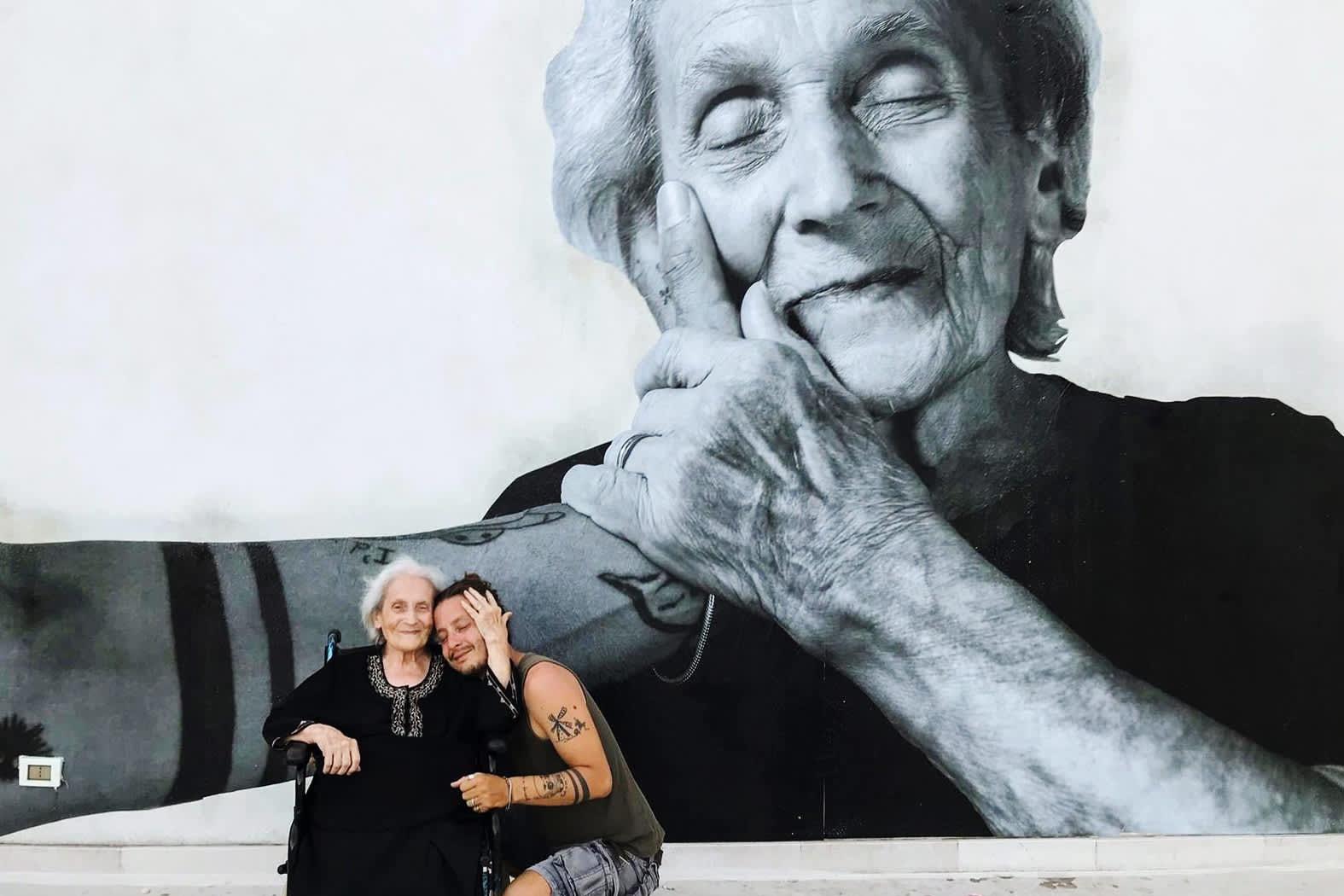 Kuvassa isoäiti ja aikuinen lapsenlapsi halaavat.