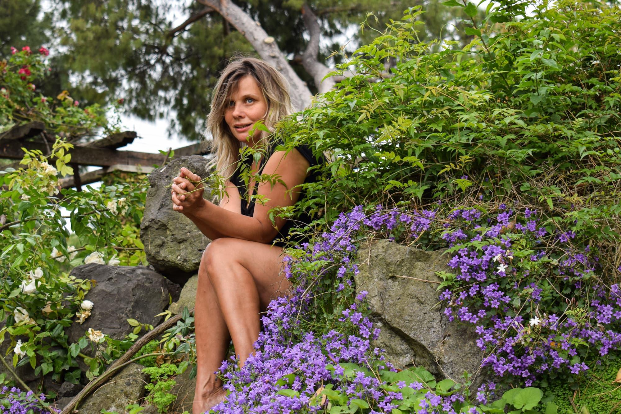 Riikka Vainio istuu puistossa kukkien keskellä.