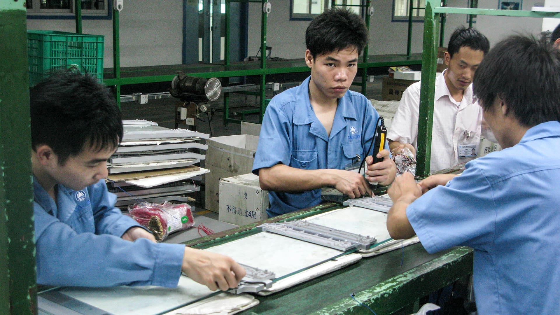 Miehiä työskentelemässä kiinalaisessa tehtaassa.