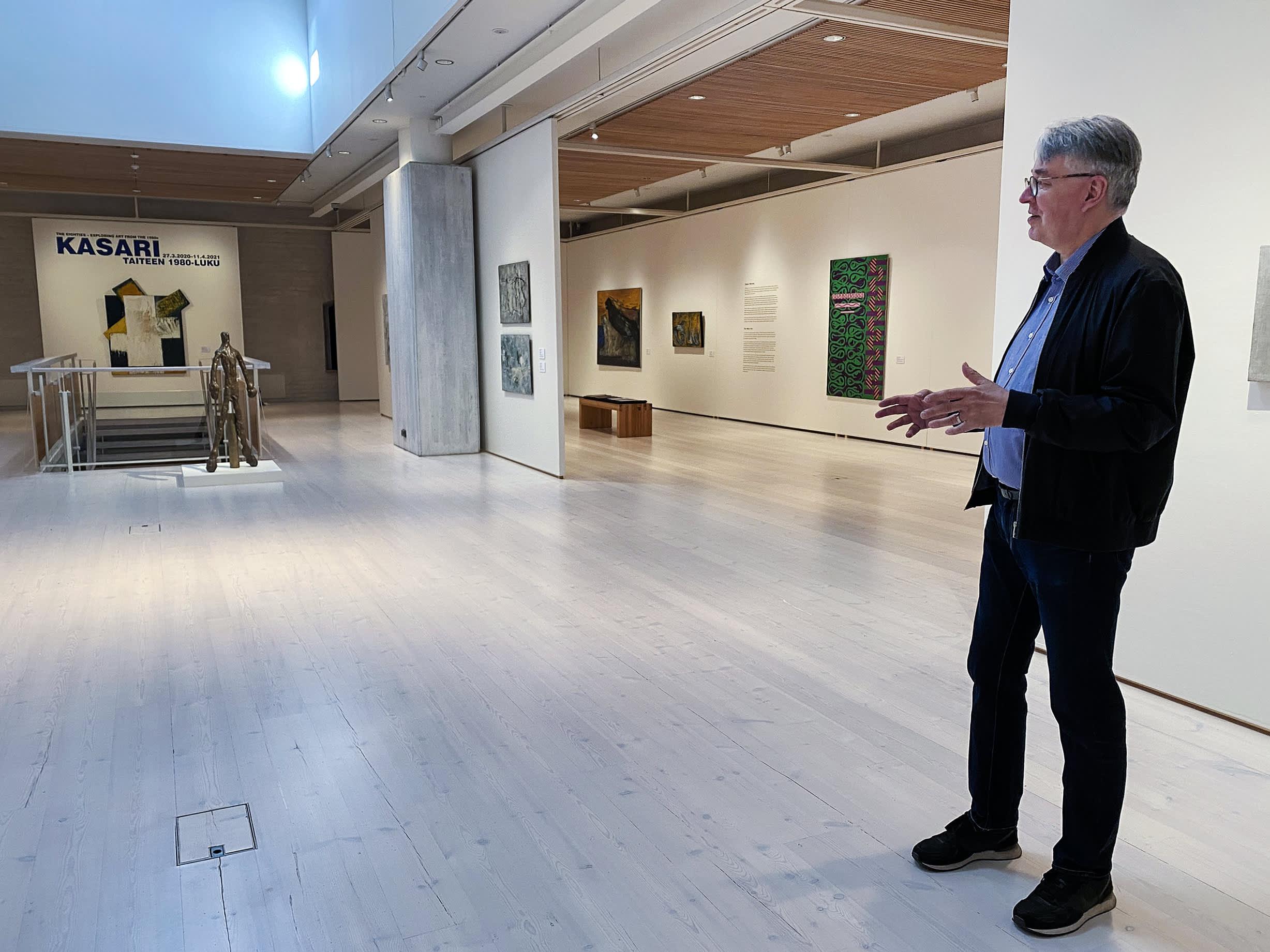 Mies kertoo taidenäyttelystä taidemuseossa.