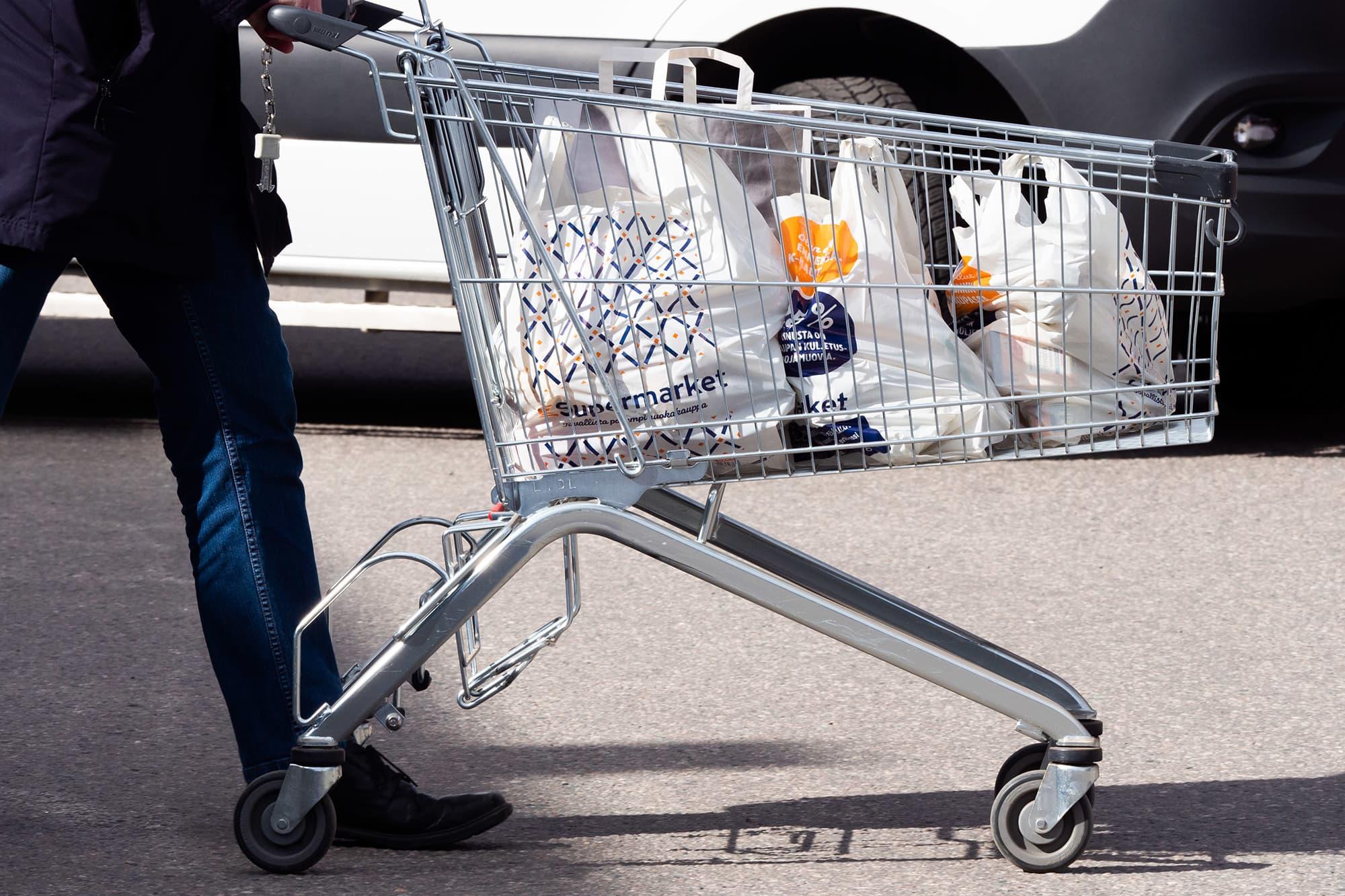 Mies työntää ostoskärryä jossa monta kassillista ruokaostoksia.