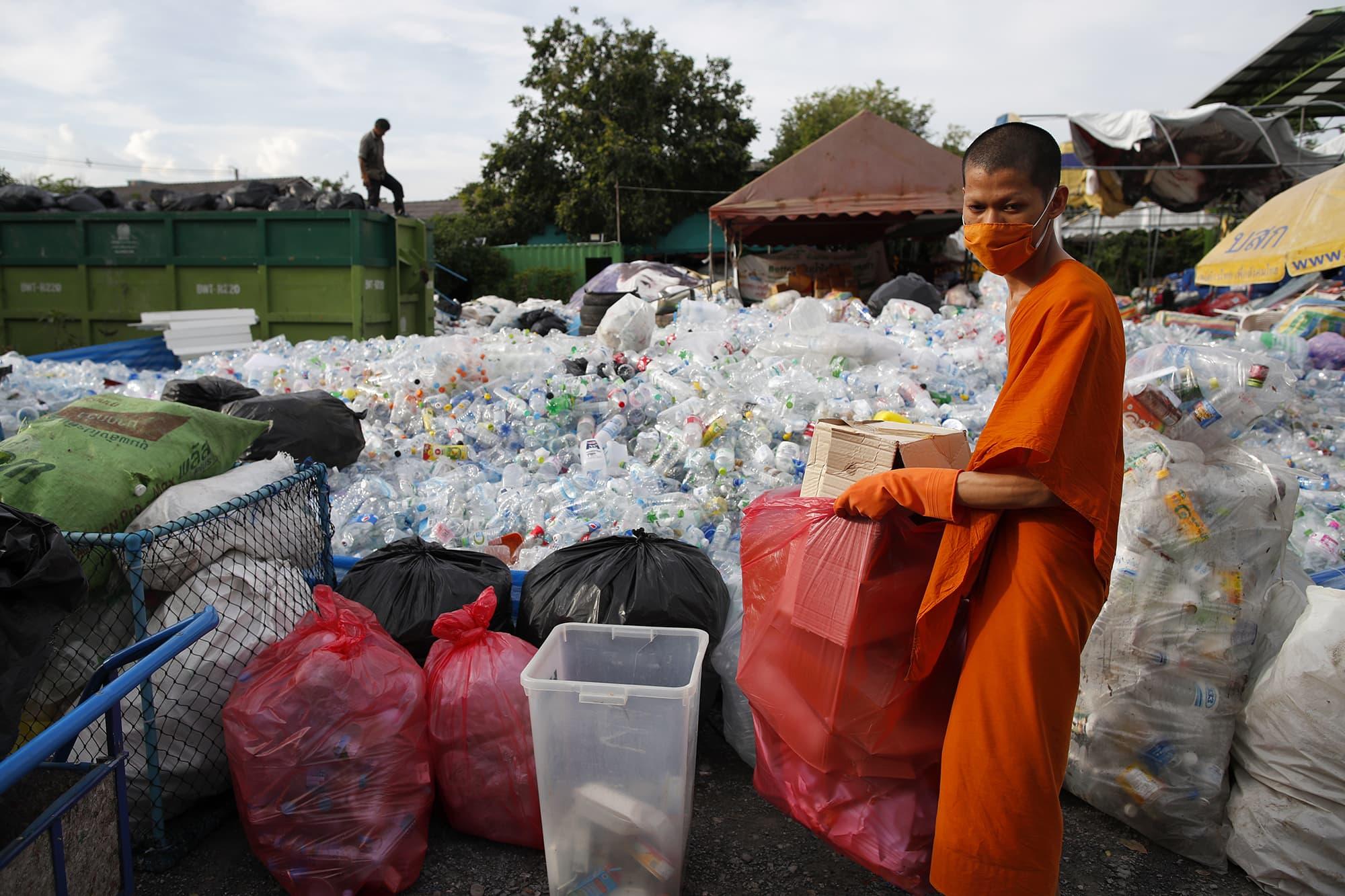 Kuvassa on munkki, joka lajittelee kierrätettävää muovijätettä.