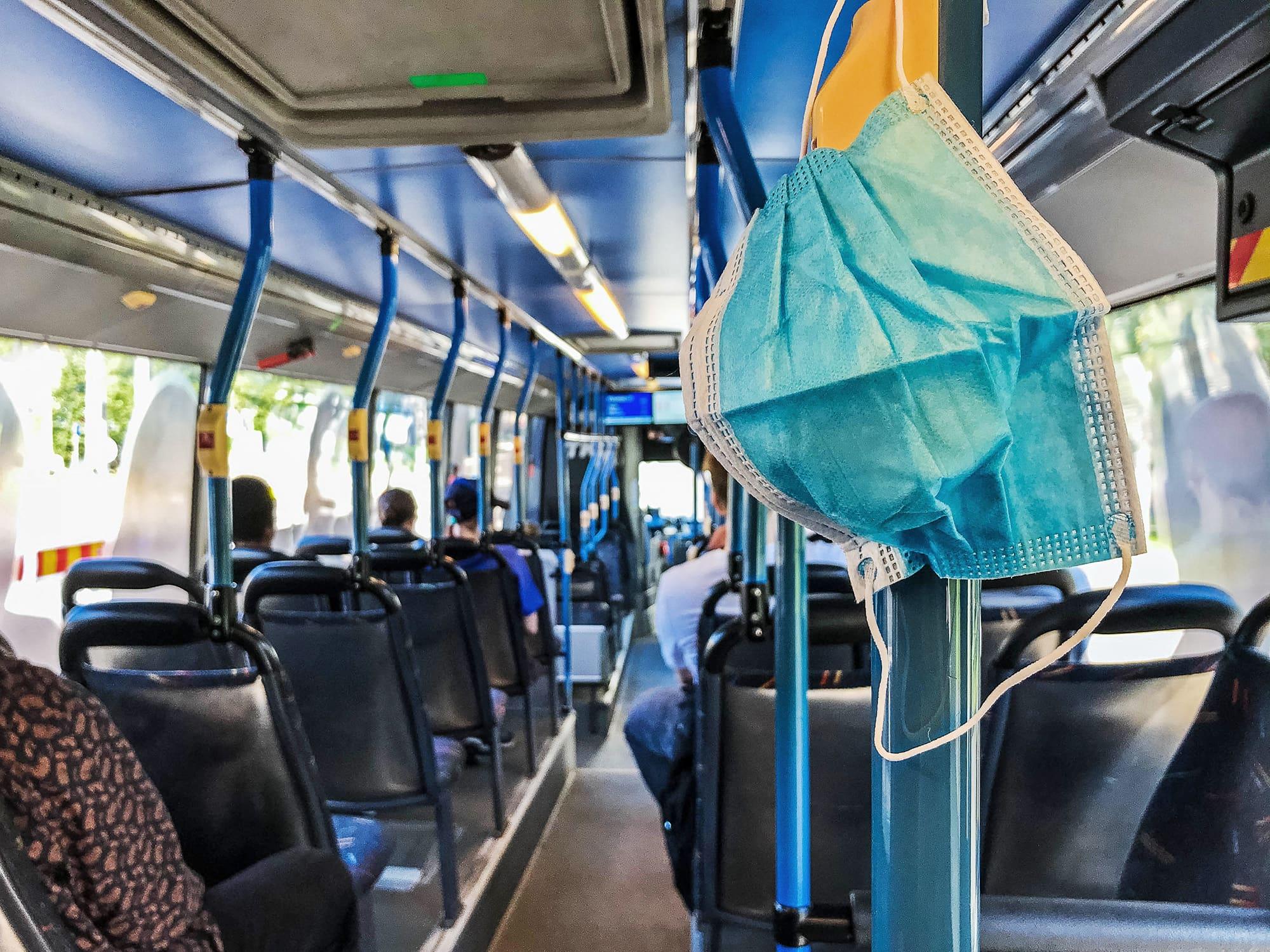 Kertakäyttöinen maski roikkuu bussin tangossa.
