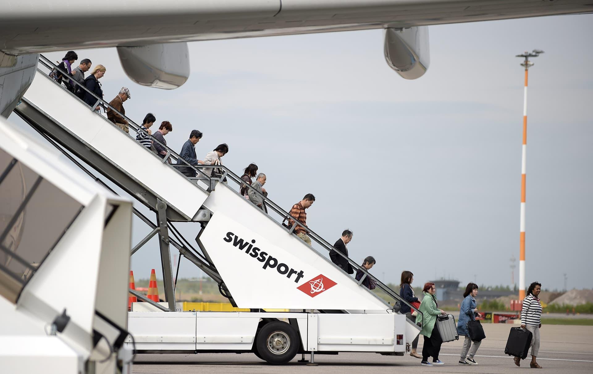 Finnairin aasianlento saapunut Helsinki-Vantaan lentokentällä. Matkustajat poistuvat swissportin rappujen kautta platalle.