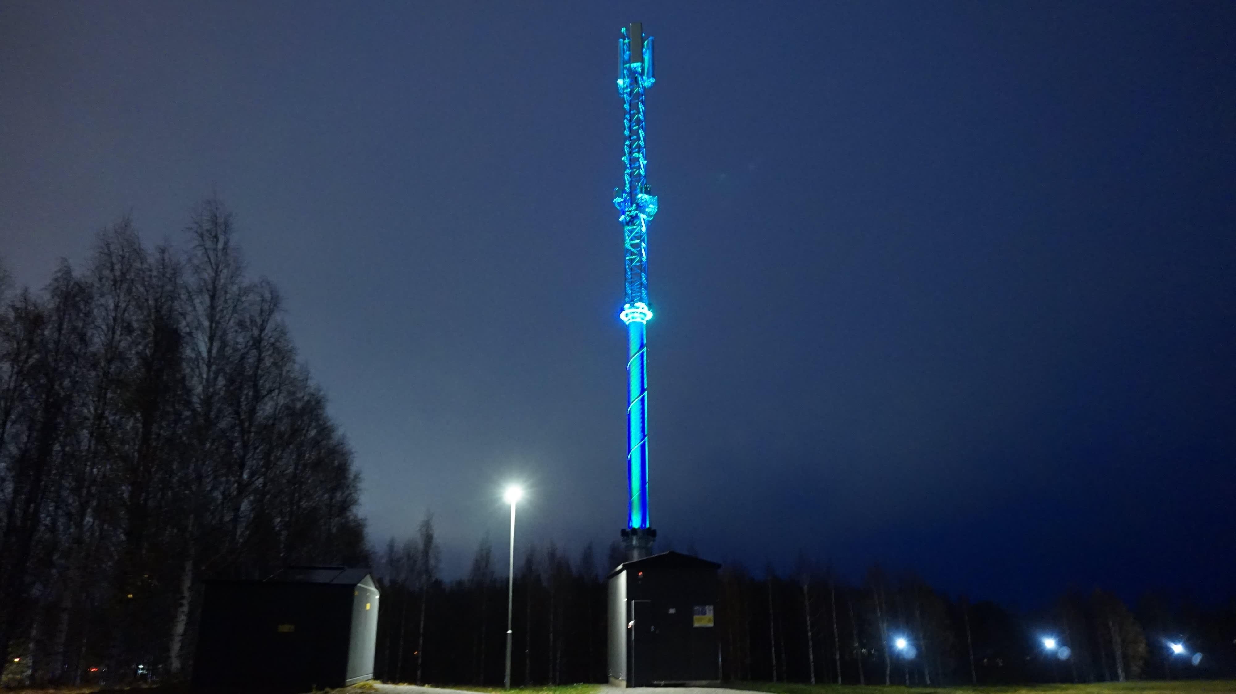 Sinivihreäksi valaistu tietoliikennemasto kohoaa Joensuun Linnunlahdella.