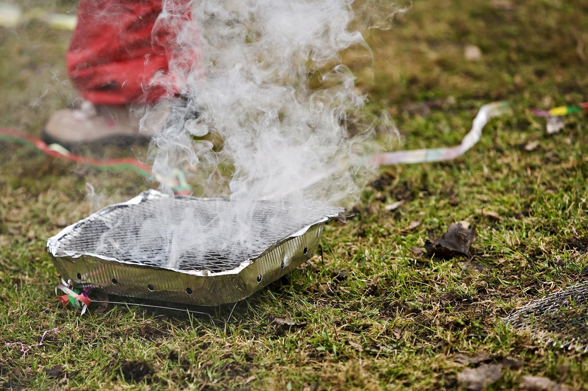 Kertakäyttögrilli savuttaa nurmikolla.