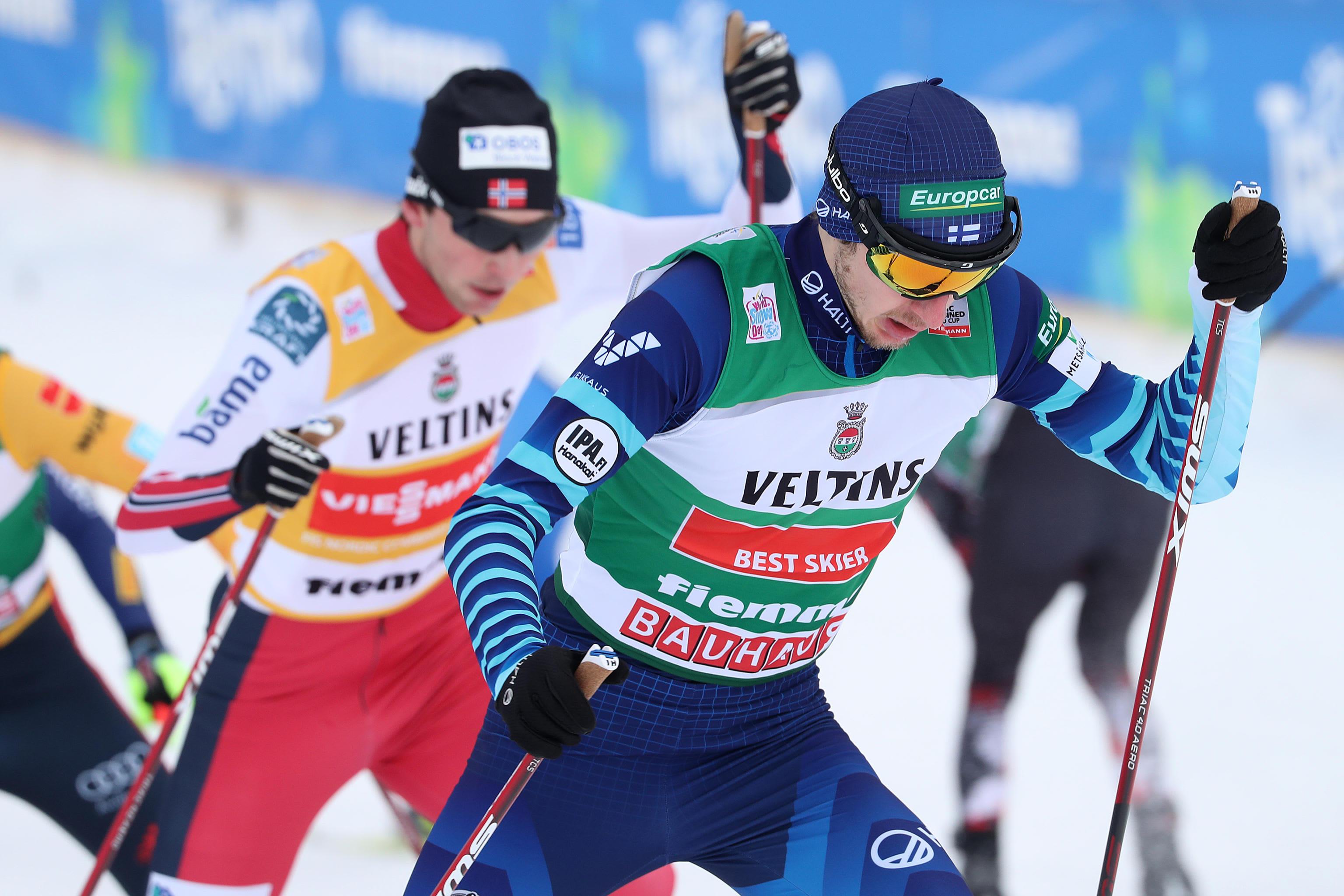 Ilkka Herola hiihtää ylämäkeä Jarl Magnus Riiberin edessä Val di Fiemmessä.