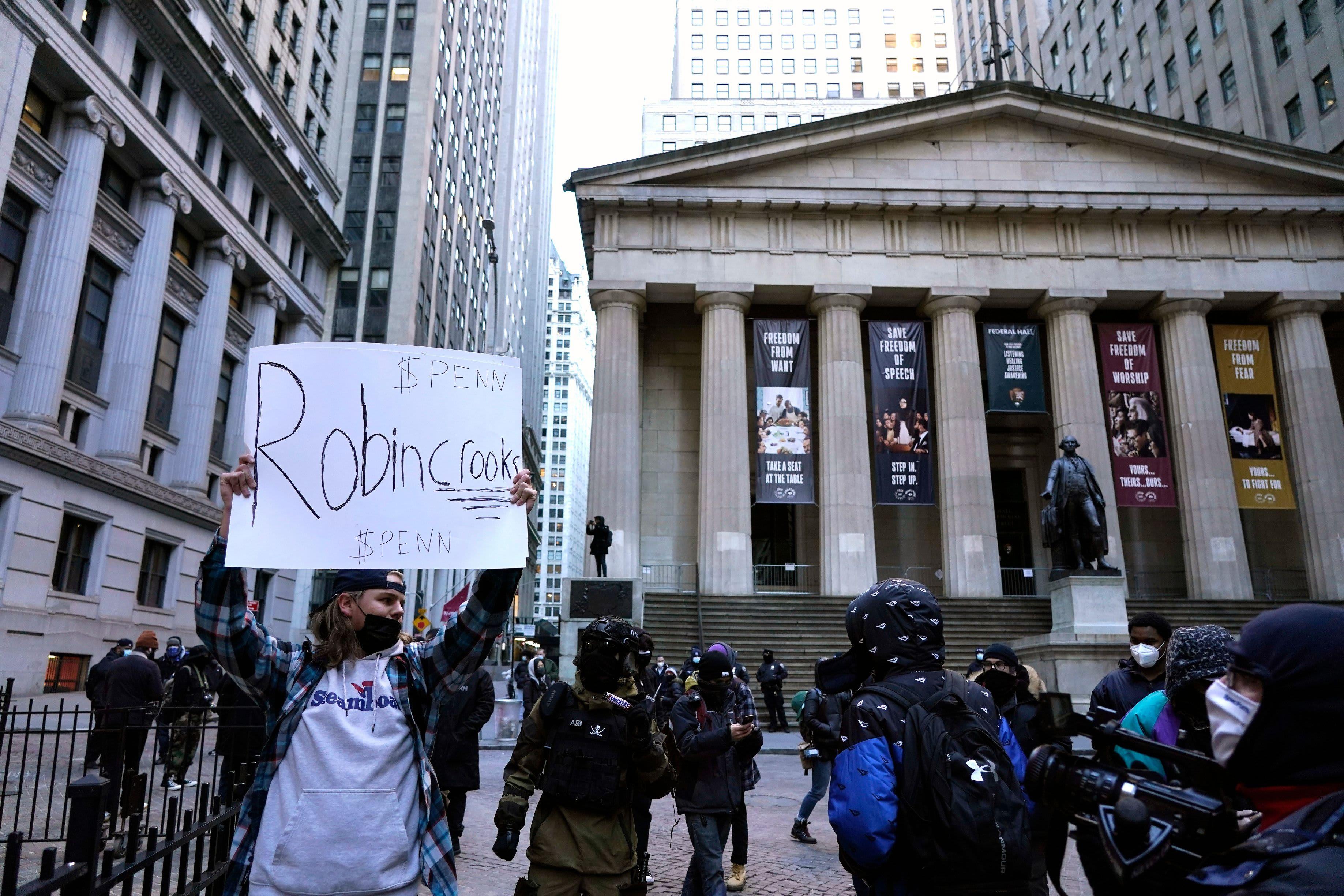 Mielenosoittaja pitelee kylttiä New Yorking pörssin edessä
