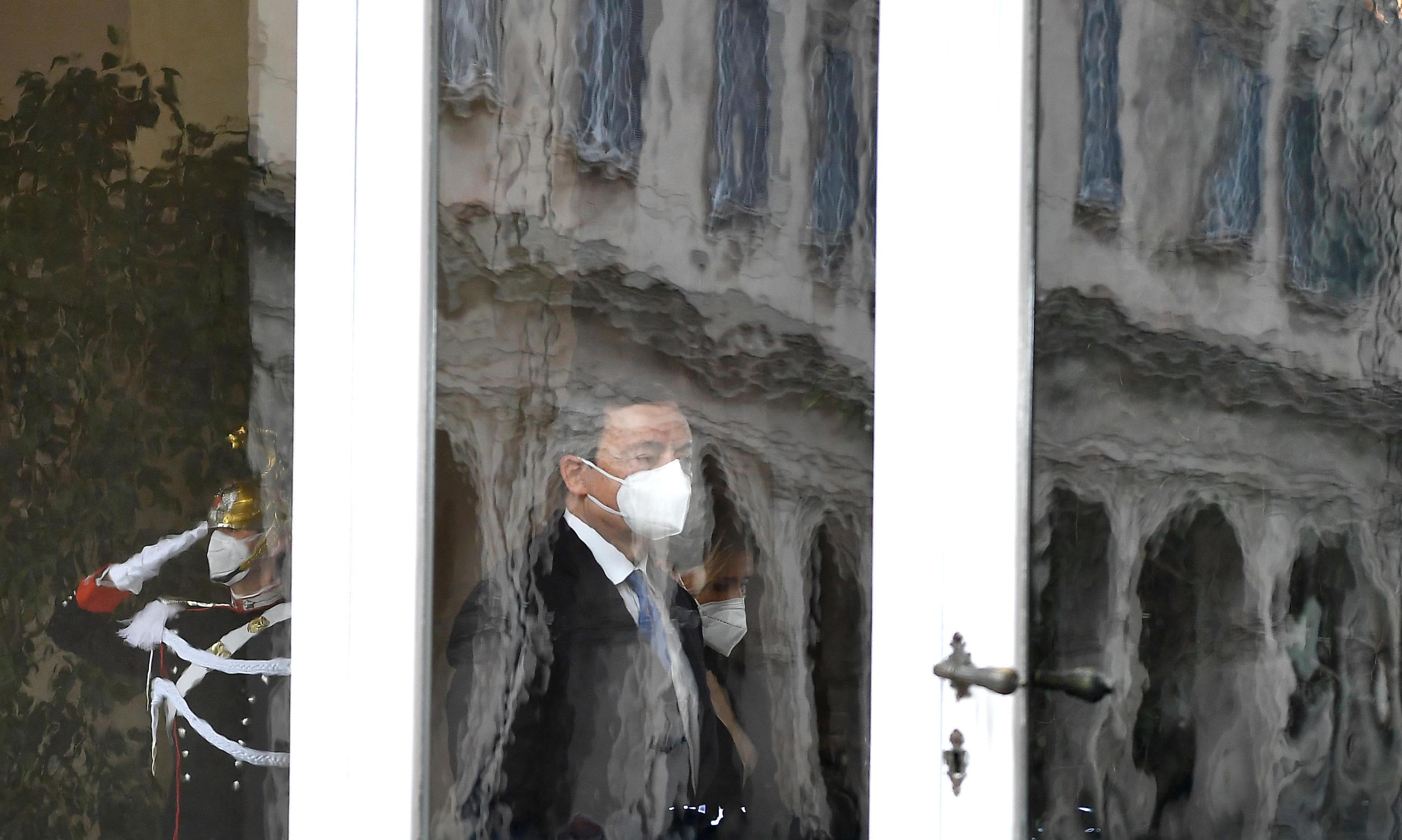 Mario Draghi ikkunalasin takana hengityssuoja kasvoillaan.