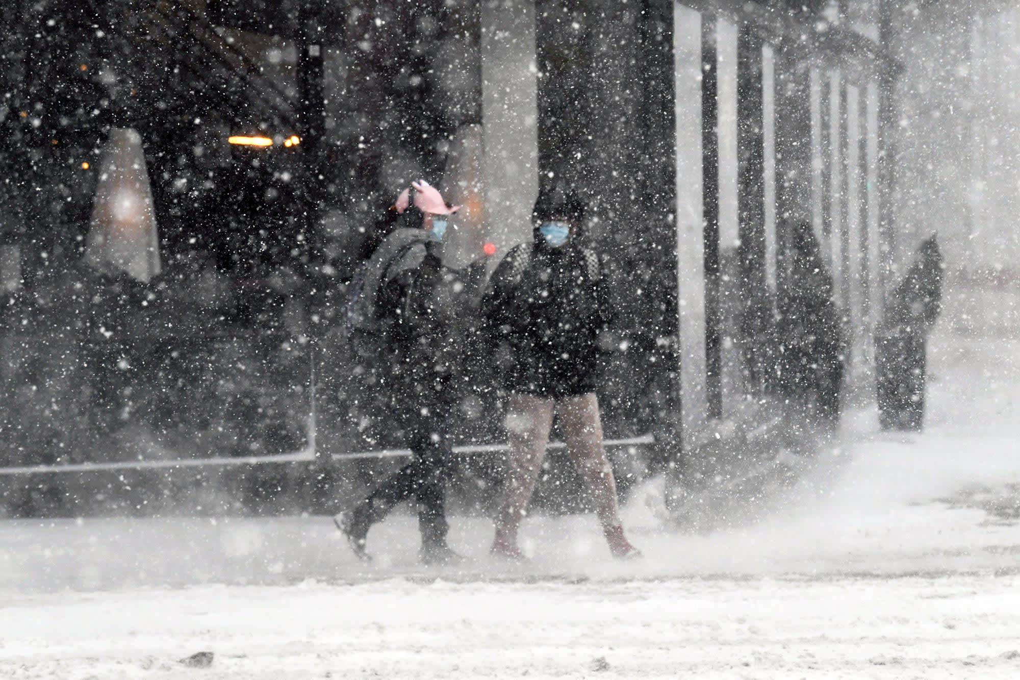 Jalankulkijoita maskit kasvoilla lumimyräkässä Helsingissä.