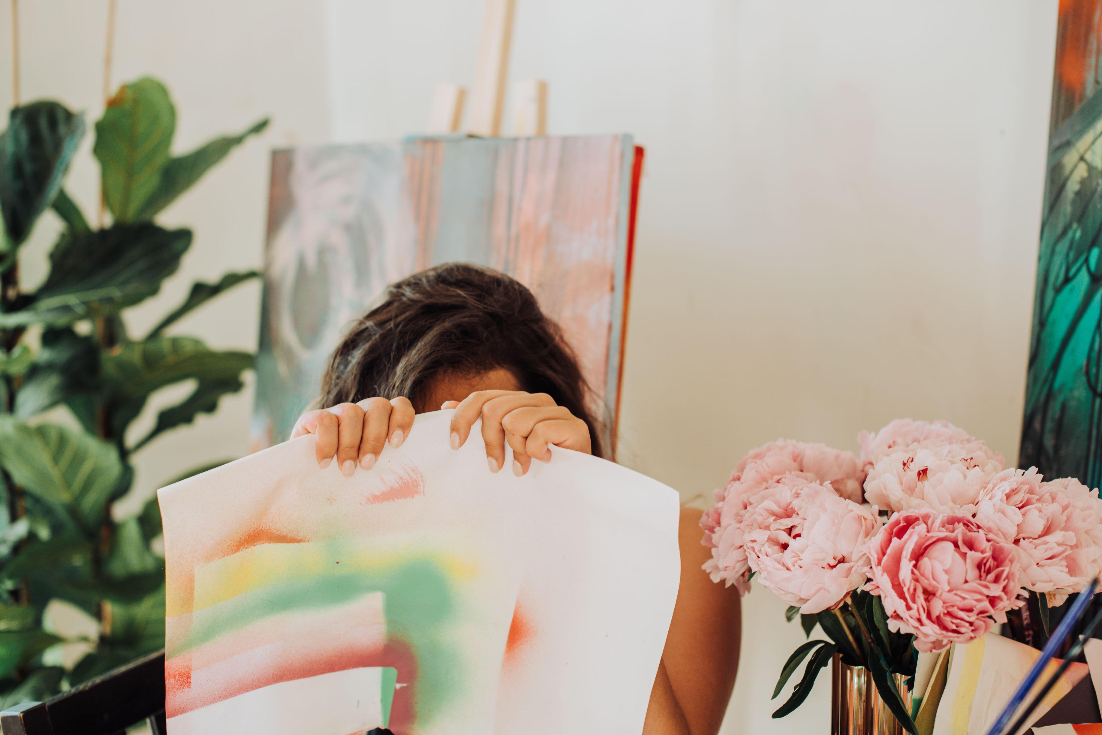 Nainen piileskelee vesivärimaalauksen takana