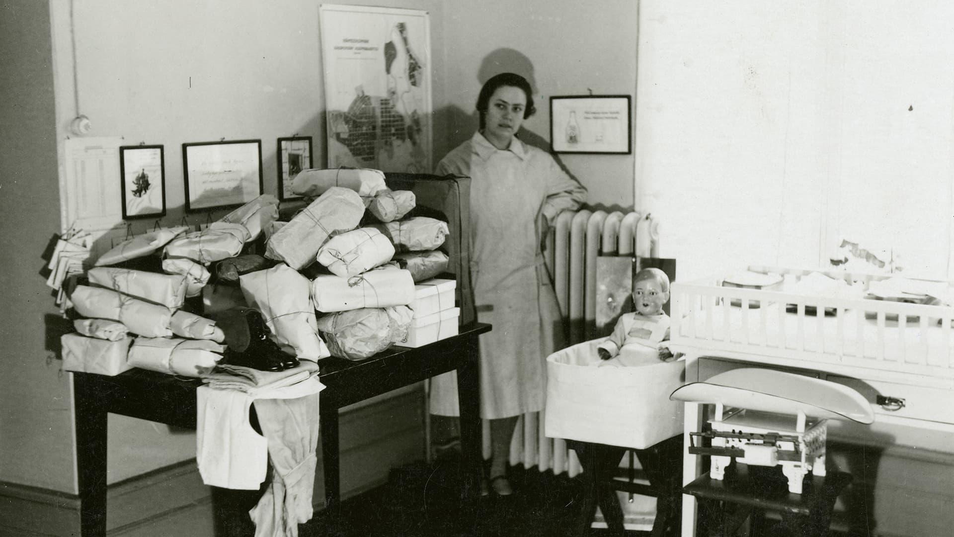 Arkistokuvassa hoitaja ja lastenhoitoon liittyvää esineistöä.