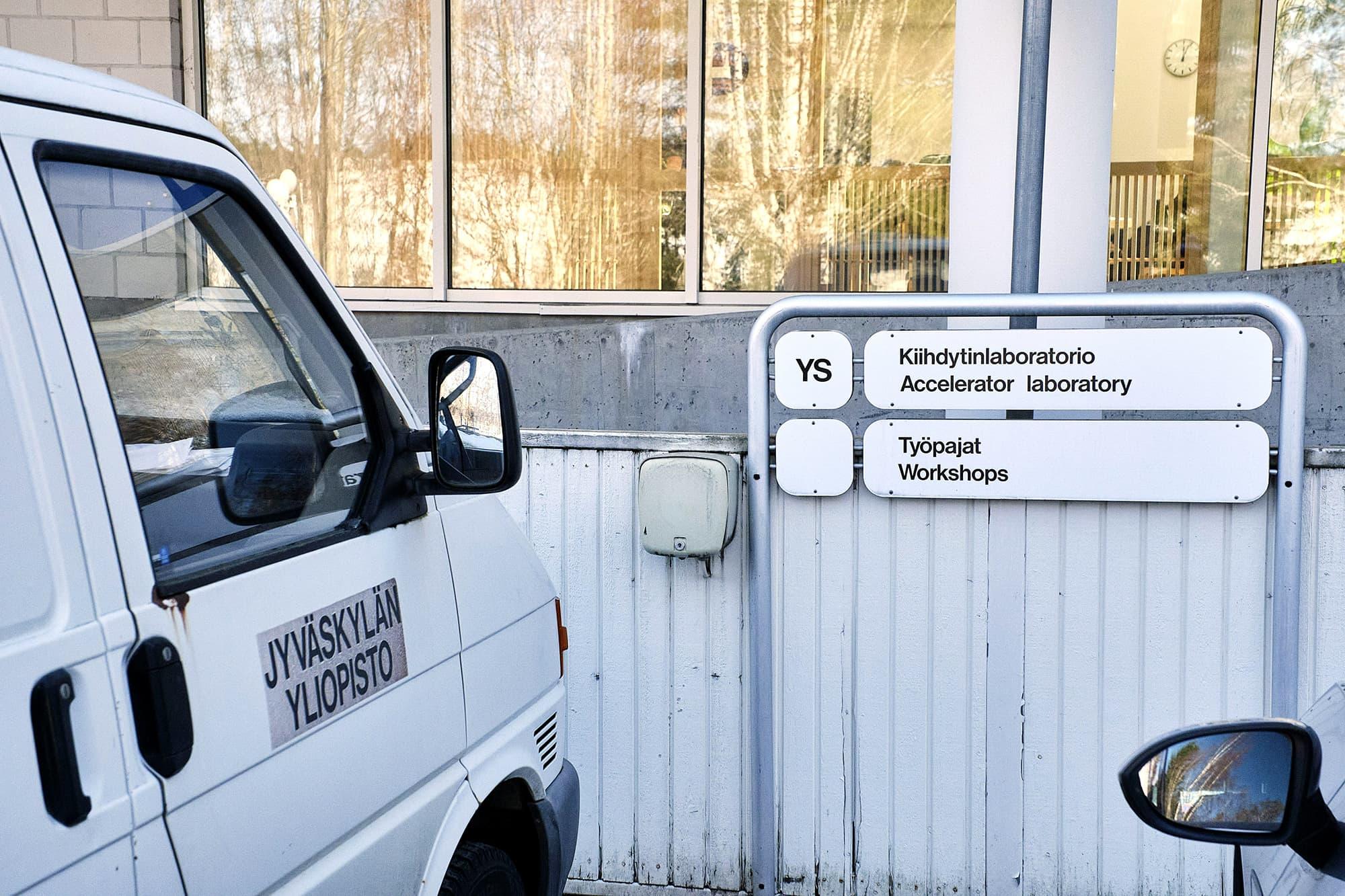 Kiihdytinlaboratorio -kyltti yliopiston parkkipaikalla.
