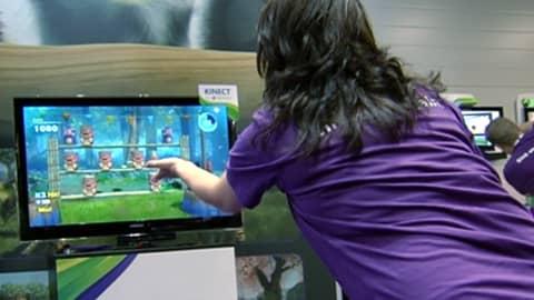 Tyttö ohjaa videopeliä käsillään.