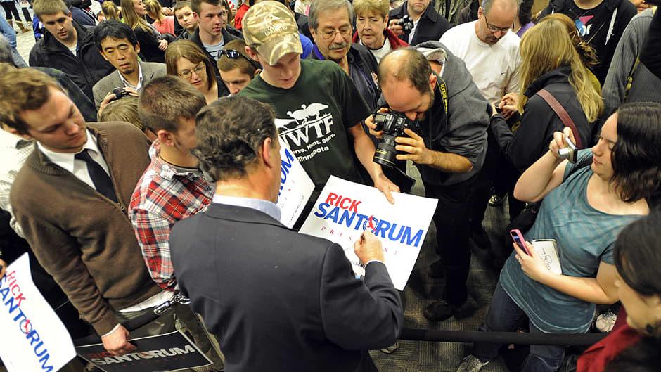 Rick Santorum jakaa nimikirjoituksia ja puhuu kannattajiensa kanssa kampanjatapahtumassa.