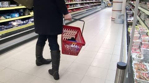 Nainen kantaa ostoskoria kaupan käytävällä.
