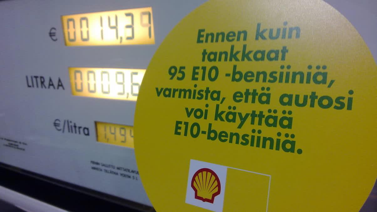 Varoitustarra bensiinimittarissa.