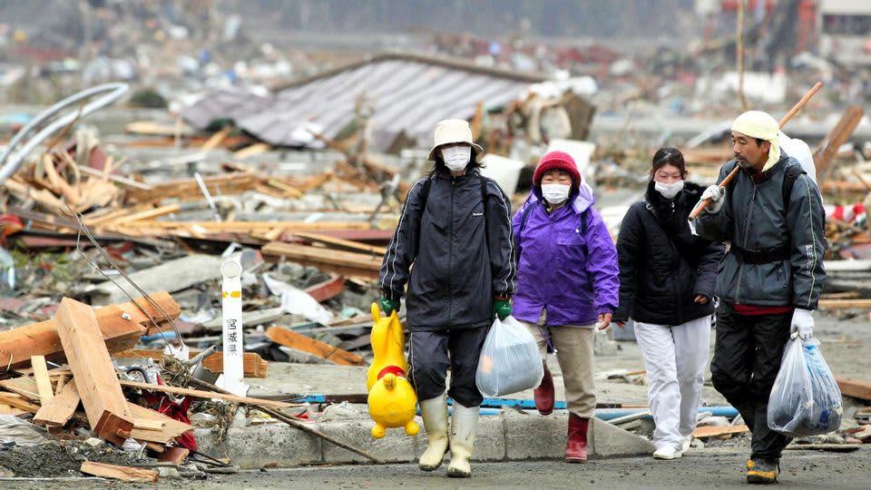 Nelihenkinen perhe muovikassit käsissään raunioituneen kaupungin keskellä.