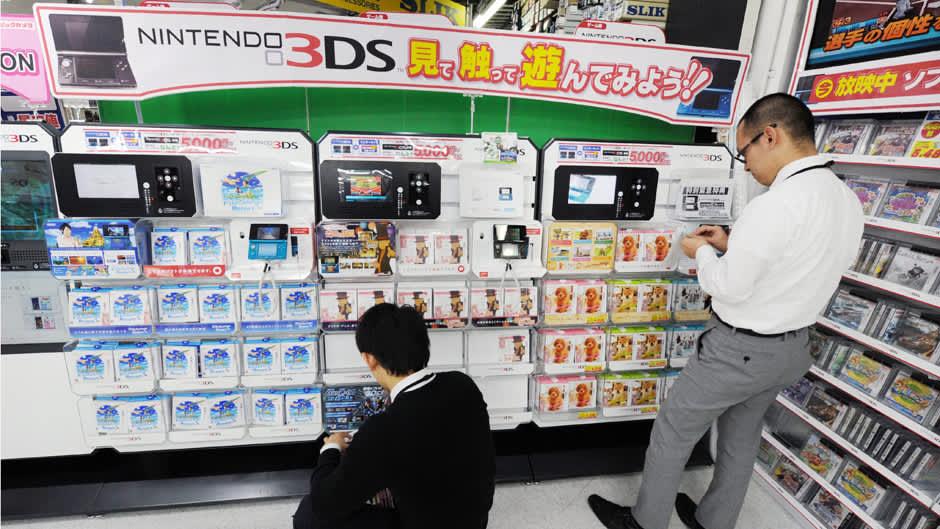 Japanilaiset pelikaupan asiakkaat tutkivat Nintendo-pelejä Tokiossa.