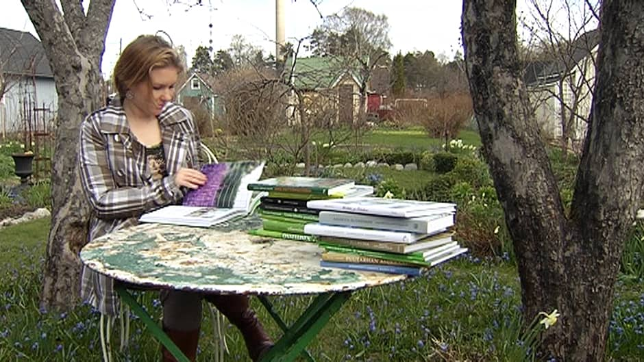 Nainen lukee kirjoja puutarhassa.
