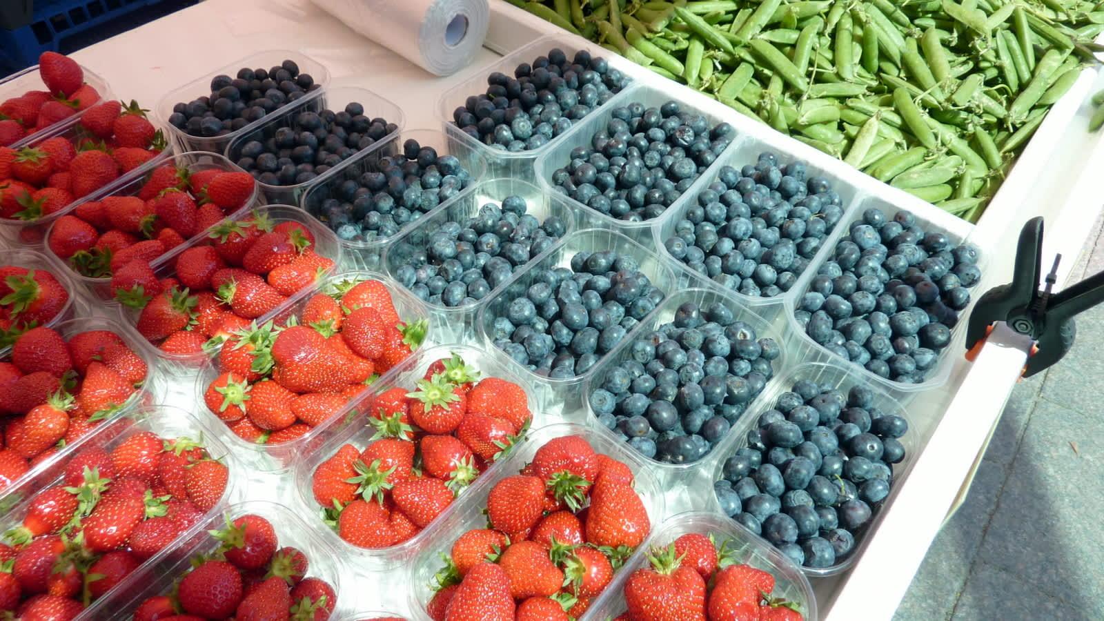 Toripöydällä mansikoita, mustikoita ja herneenpalkoja.